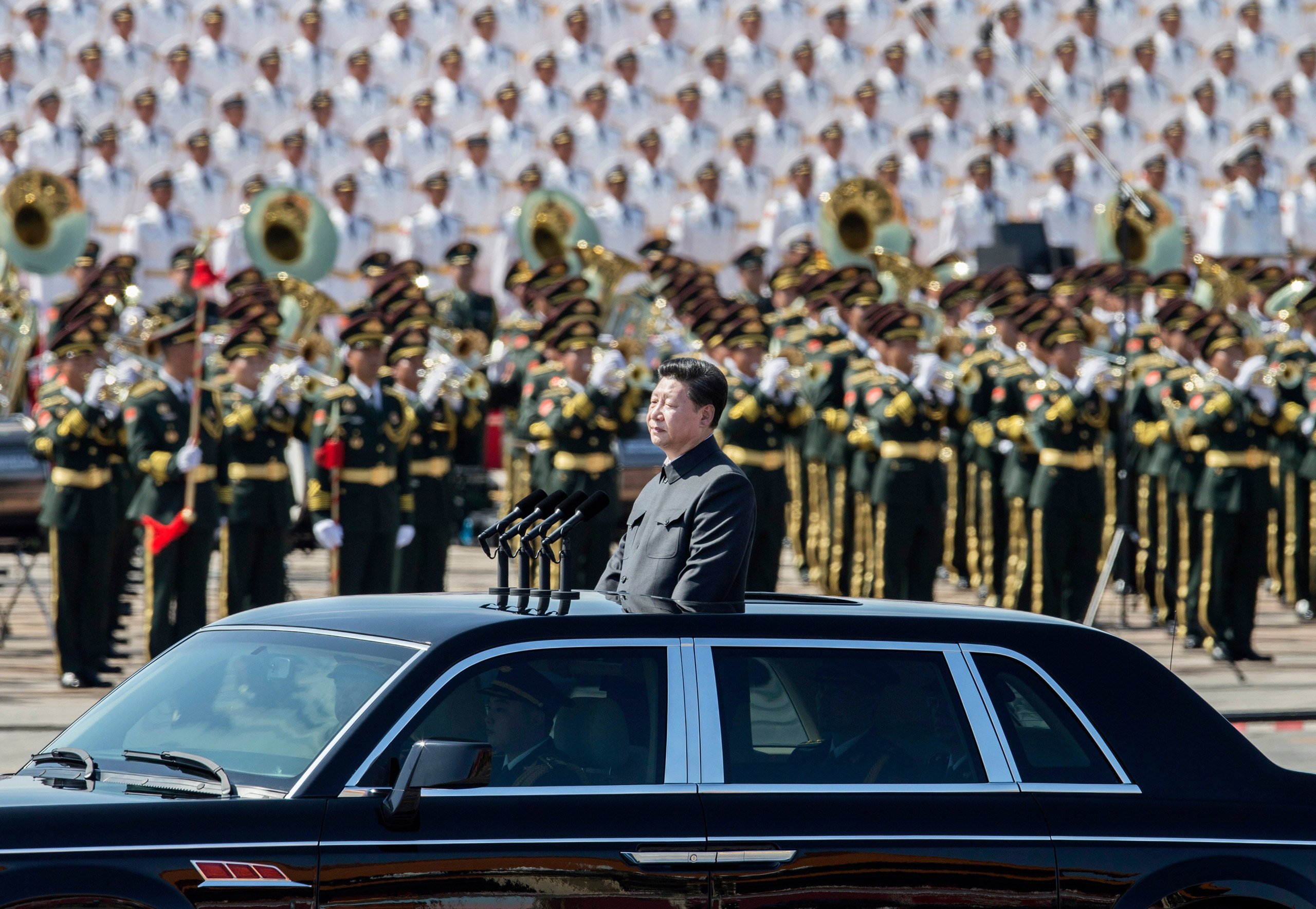 Chinese president and leader of the Communist Party Xi Jinping rides in an open top car in front of Tiananmen Square and the Forbidden City during a military parade in Beijing, on Sept. 3, 2015.