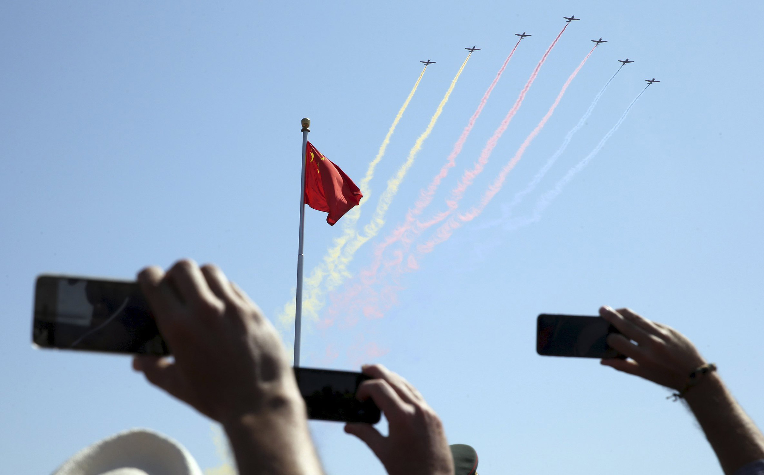 People record trainer jets flying over Tiananmen Square during a military parade to mark the 70th anniversary of the end of World War II in Beijing, on Sept. 3, 2015.