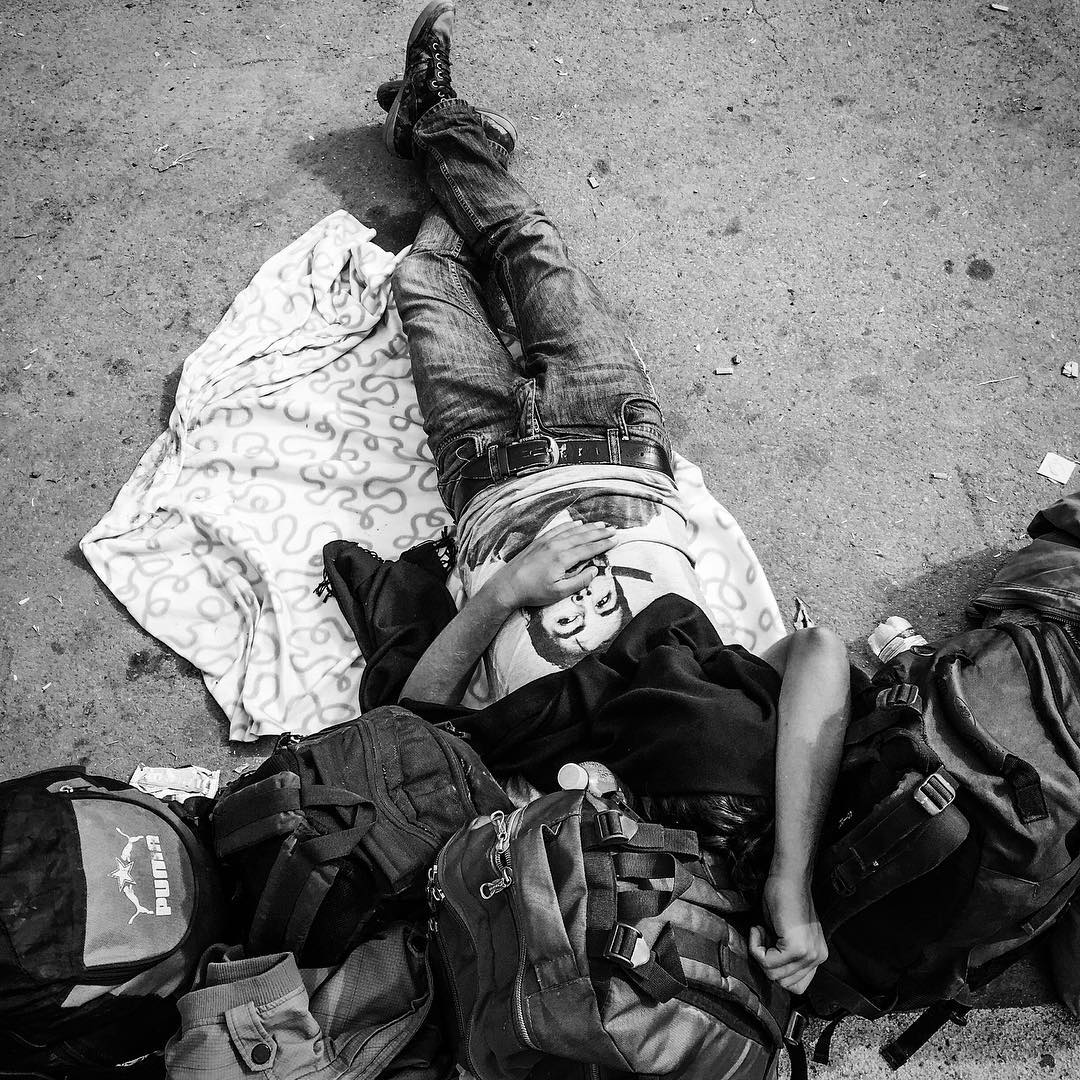 A refugee sleeps while waiting in line for a bus in Tovarnik, Croatia. Sept. 20, 2015.