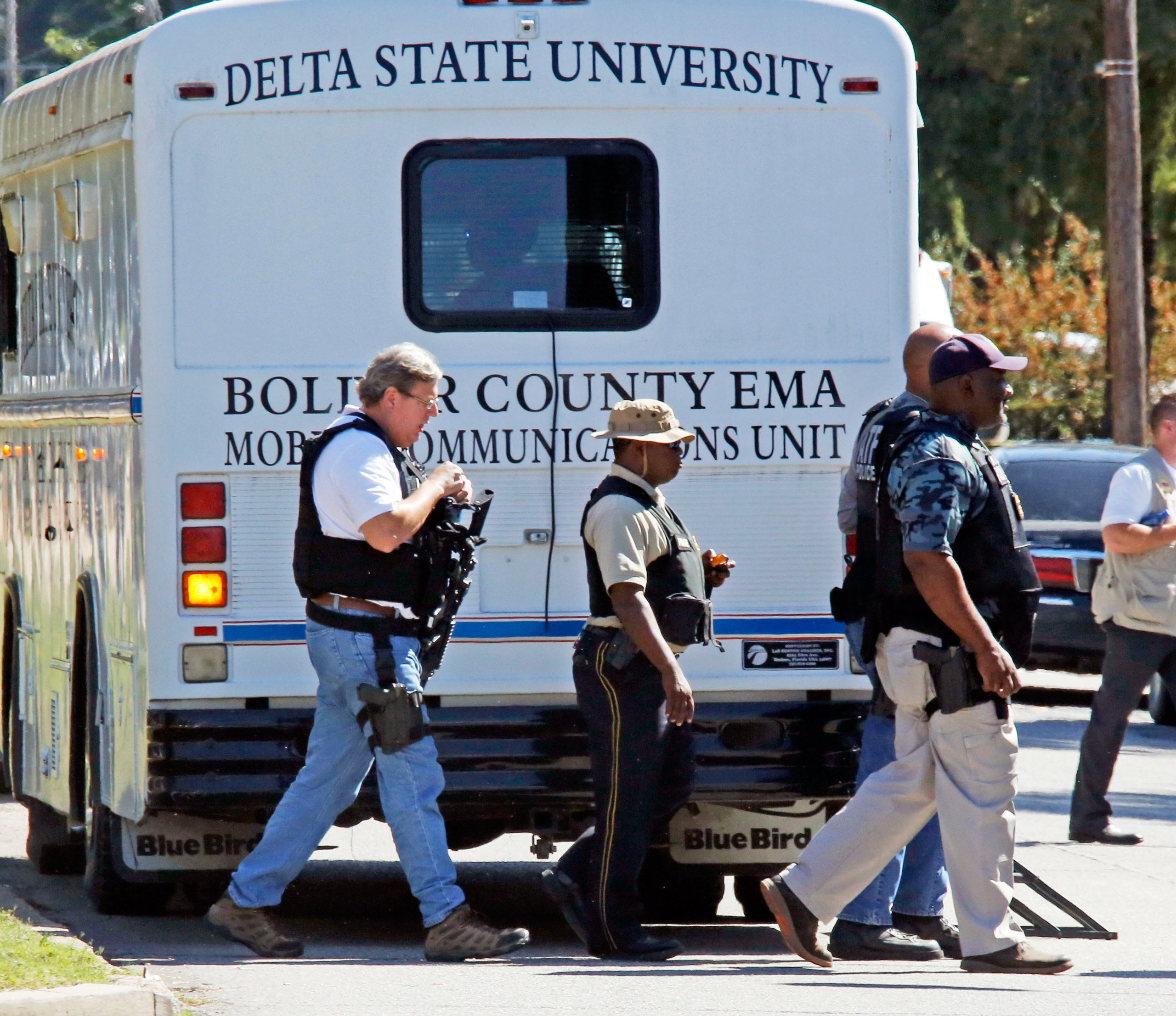 Law enforcement walk across the Delta State University campus to search for an active shooter in connection with the shooting of history professor Ethan Schmidt at Delta State University in Cleveland, Miss., on Sept. 14, 2015.