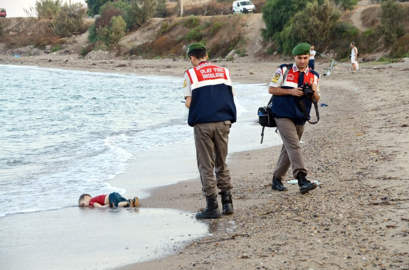 Members of the Turkish gendarmerie stand near by the washed-up body of a refugee child who drowned during a failed attempt to sail to the Greek island of Kos, at the shore in the coastal town of Bodrum, Turkey, on Sept. 2, 2015. At least 11 Syrian migrants died in boat sank after leaving Turkey for the Greek island of Kos.