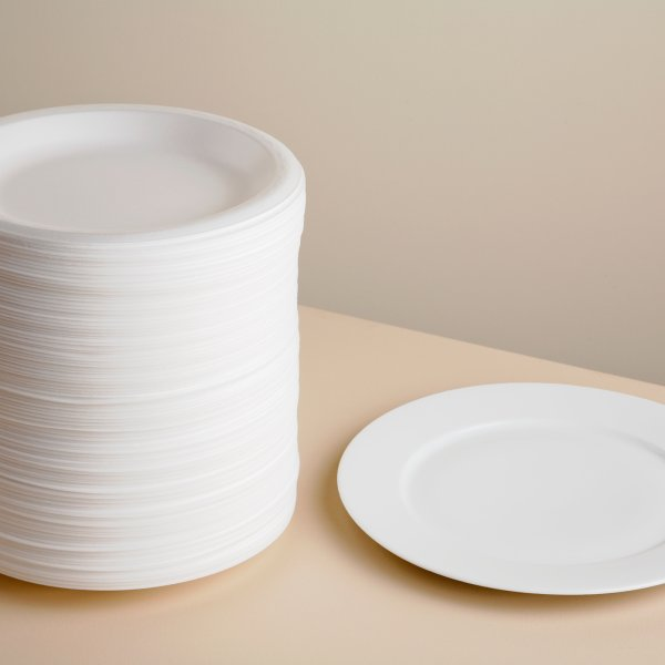 Stack of styrofoam plates and ceramic plate on table