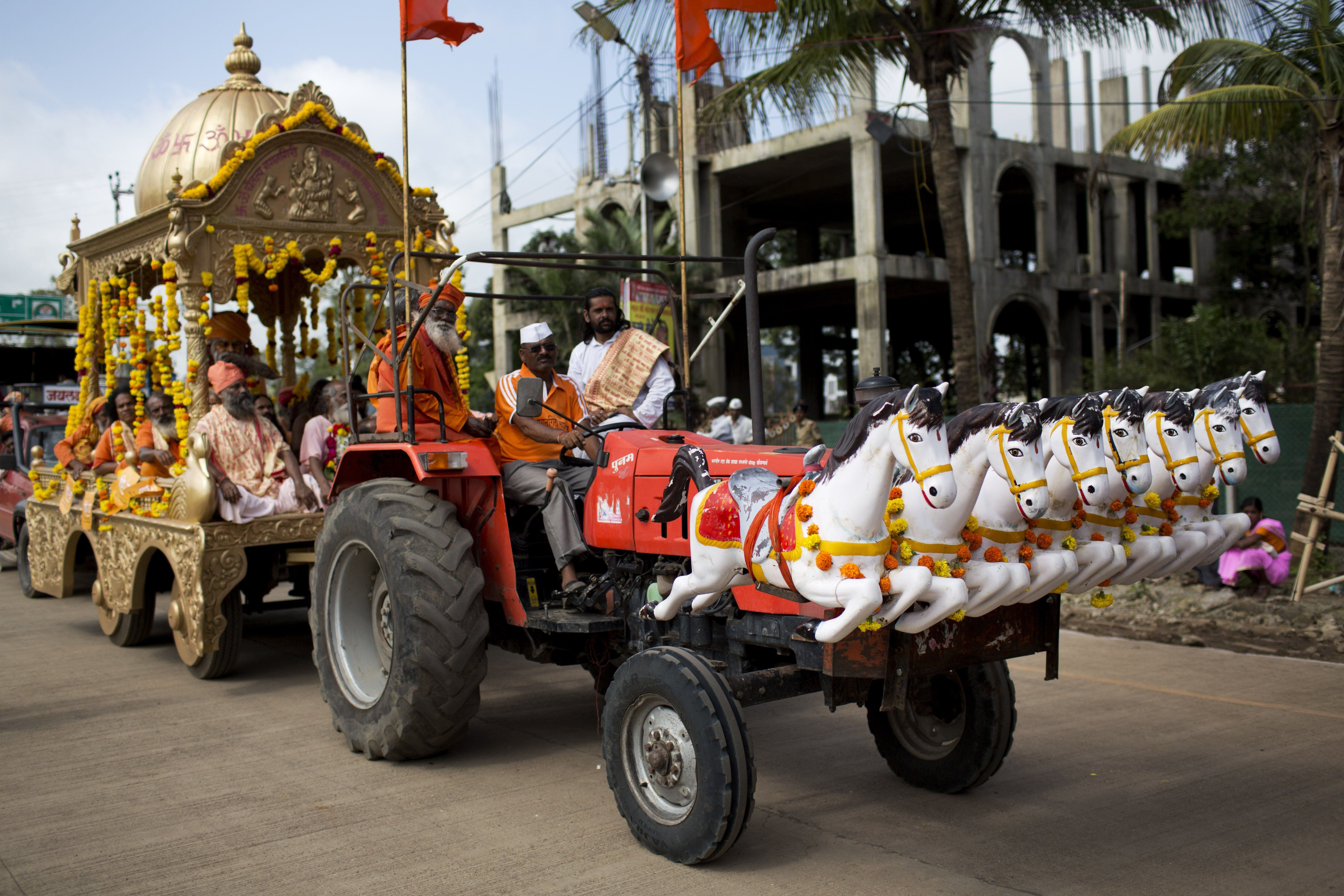 A decorated tractor pushes a carriage carrying Hindu religious men during a procession during Kumbh Mela, or Pitcher Festival, at Trimbakeshwar, India, on Aug. 27, 2015.