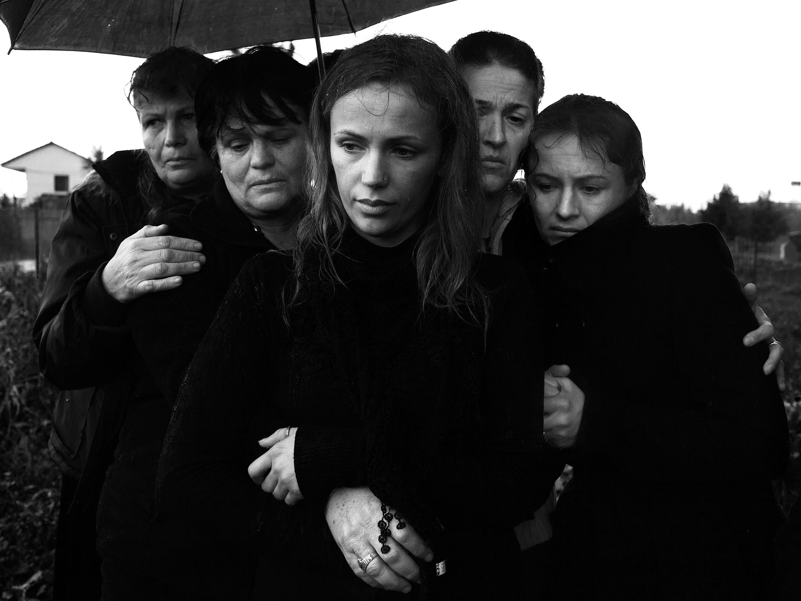 Women clustered together during a funeral. According to Albanian traditions, men and women attend funerals in separate groups.                     Tirana, Albania, 2012.