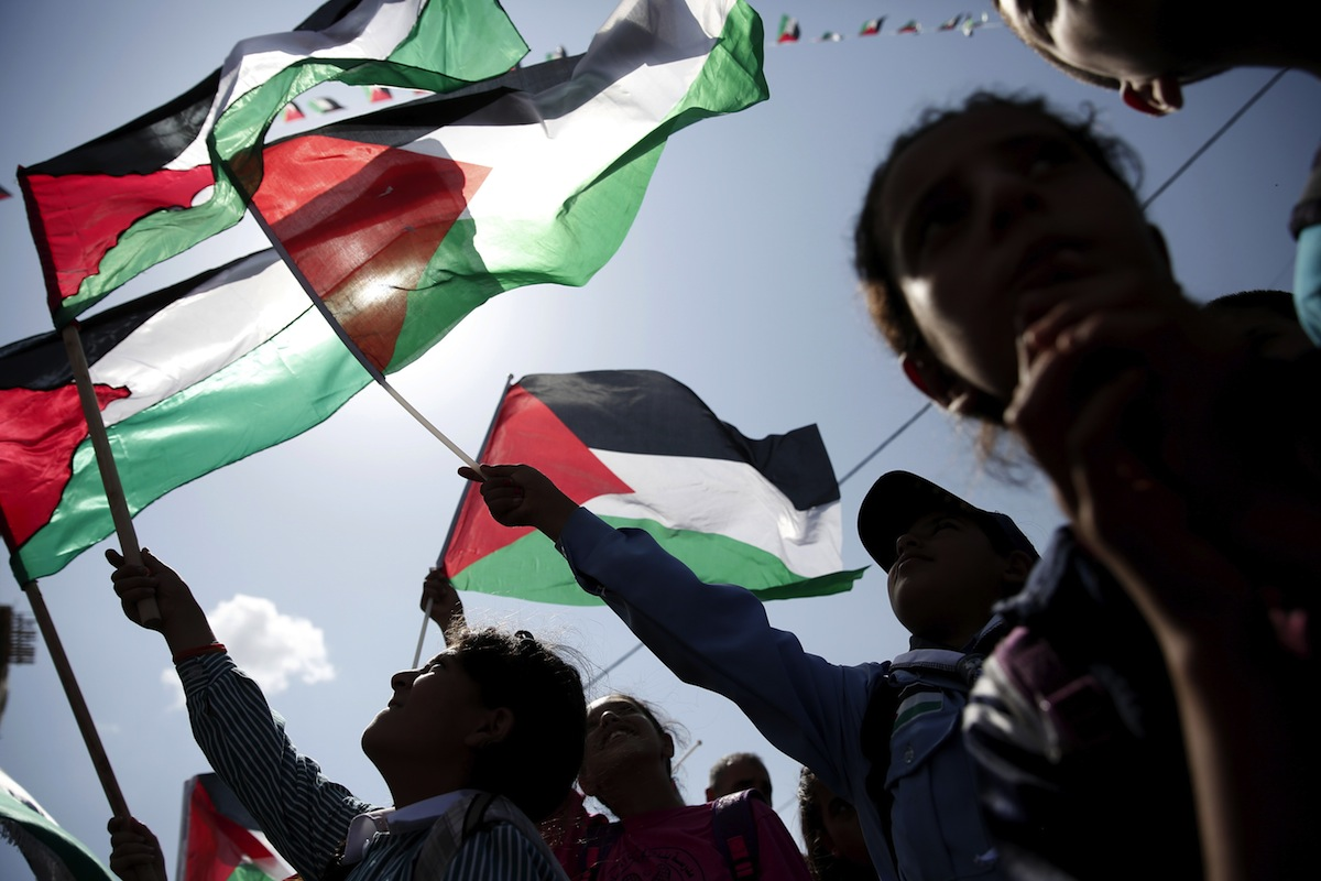 Palestinians wave their flags as they watch a live-screening of president Mahmud Abbas' speech followed by the raising of the Palestinian flag at the United Nations headquarters in New York City, on Sept. 30, 2015 in the city of Ramallah.