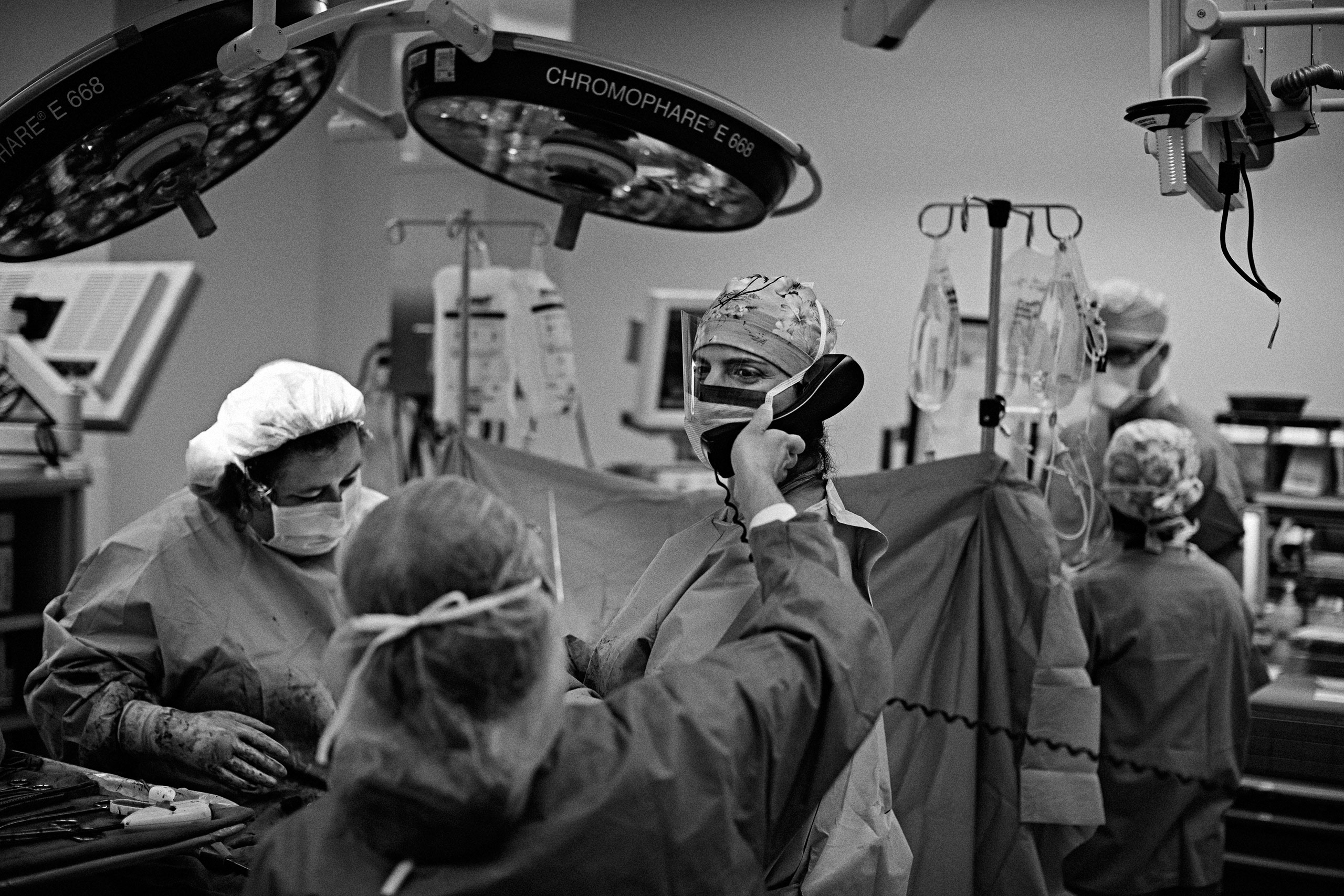 Dr. Arghavan Salles (Center) and Dr. Adela Garland (Left) in the operating room. Dr. Salles is on the phone canceling her dinner plans with her mother as the surgery has been prolonged by hours as a larger than expected tumor was discovered inside the patient.From  See the Grueling Life of an American Surgeon