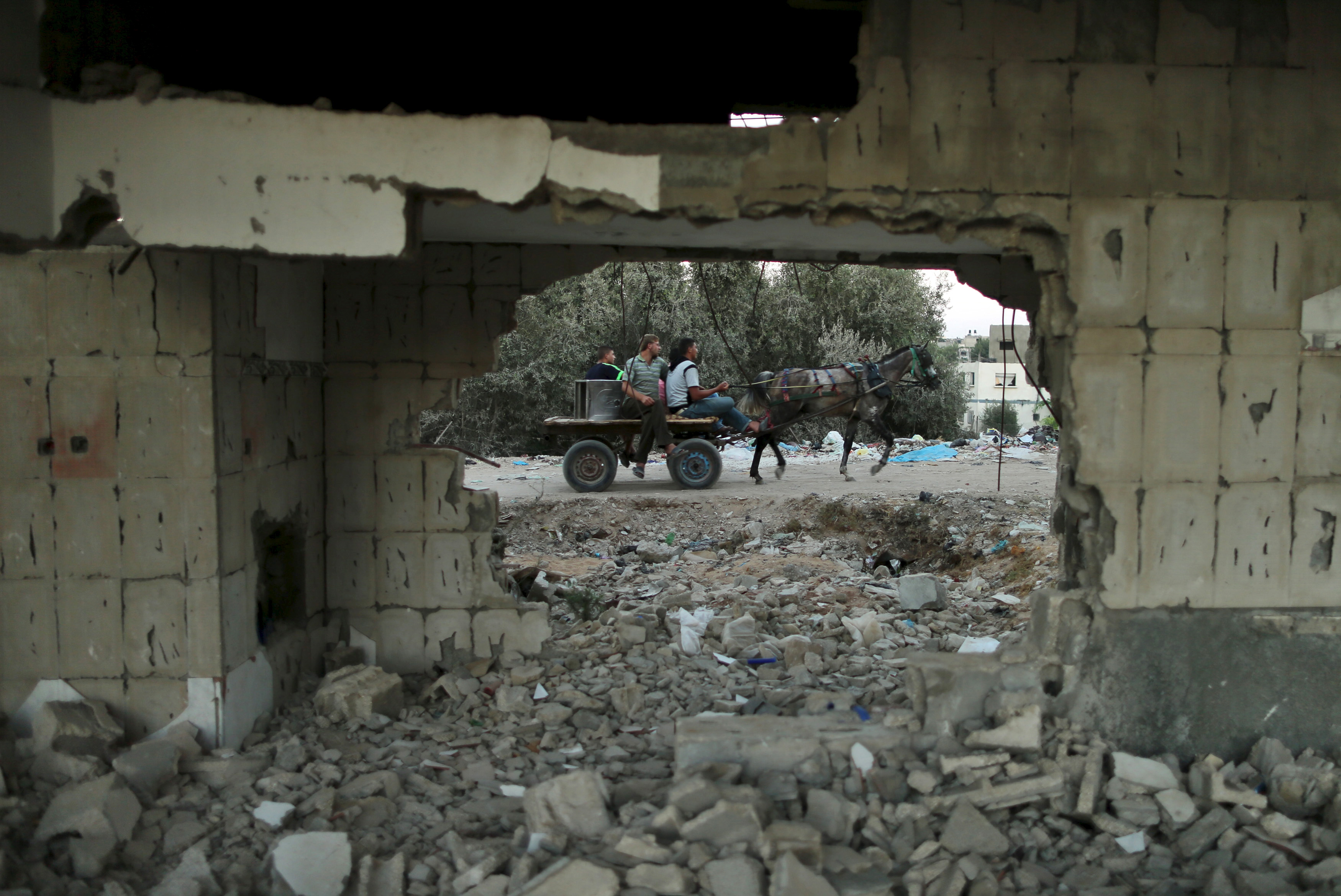 Palestinians ride a horse cart past a house, that witnesses said was destroyed by Israeli shelling during a 50-day war last summer, in Beit Lahiya town in the northern Gaza Strip on Aug. 25, 2015.