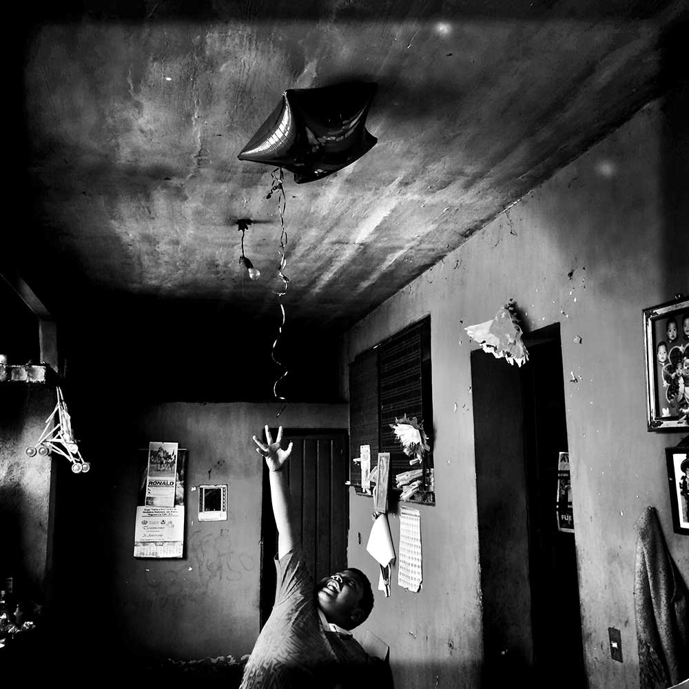 Angel tries to grab the star balloon his aunt had just brought home from work. Tixtla de Guerrero, Mexico, March 24, 2015.