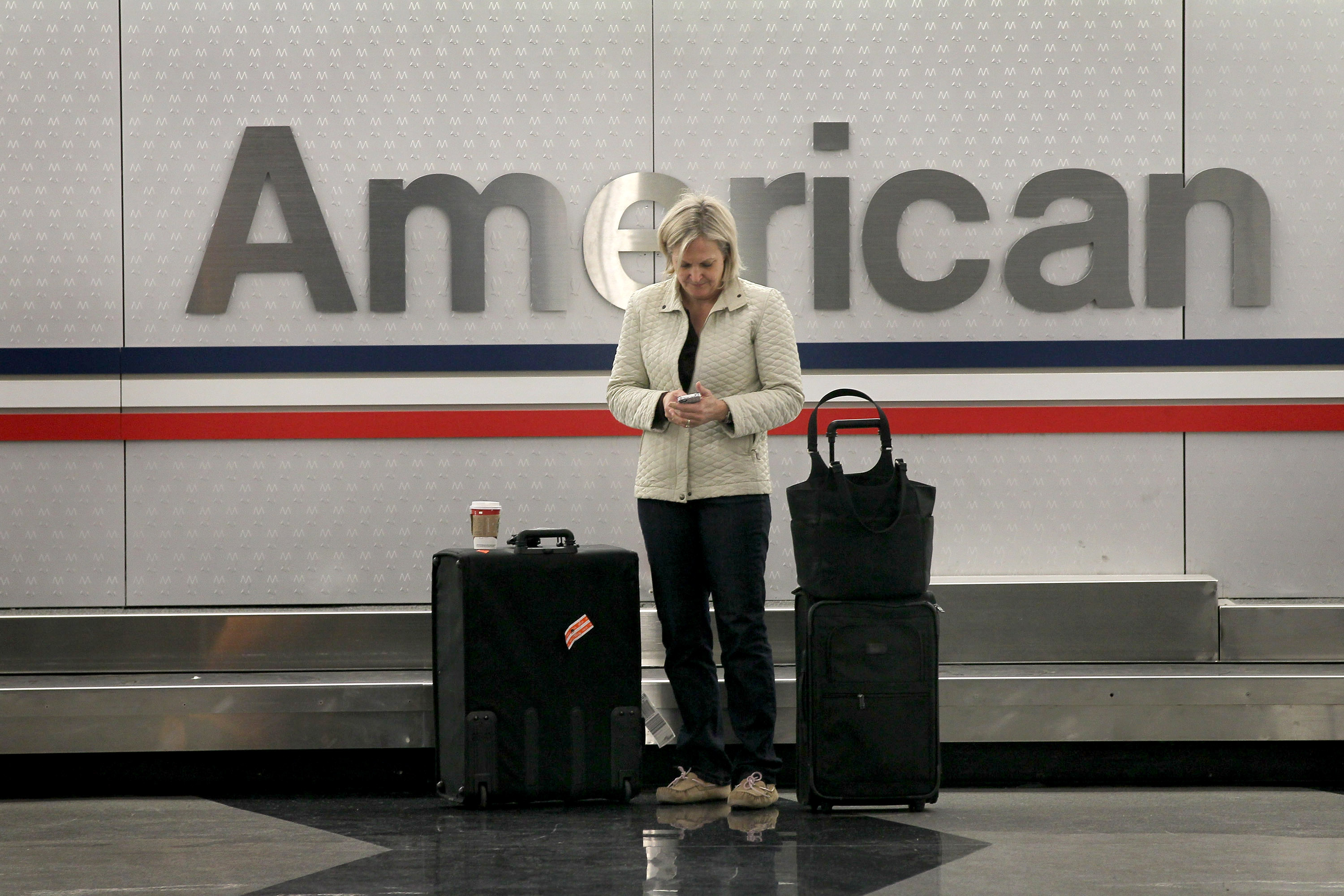 An American Airlines passenger waits for her luggage at O'Hare Airport in Chicago.