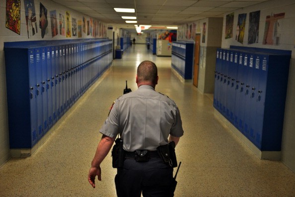 SPRINGFIELD, VA - JANUARY 18:                     Officer Joe Plazio, of the Fairfax County Police Department, patrols the hallways where he is stationed at West Springfield High School on Friday, January 18, 2012, in Springfield, VA.  Fairfax County has taken a variety of approaches to making schools safe.  Each of the high schools and middle schools have a Fairfax County school resource officer, who is an armed sworn officer with the Fairfax County Police.                     (Photo by Jahi Chikwendiu/The Washington Post via Getty Images)