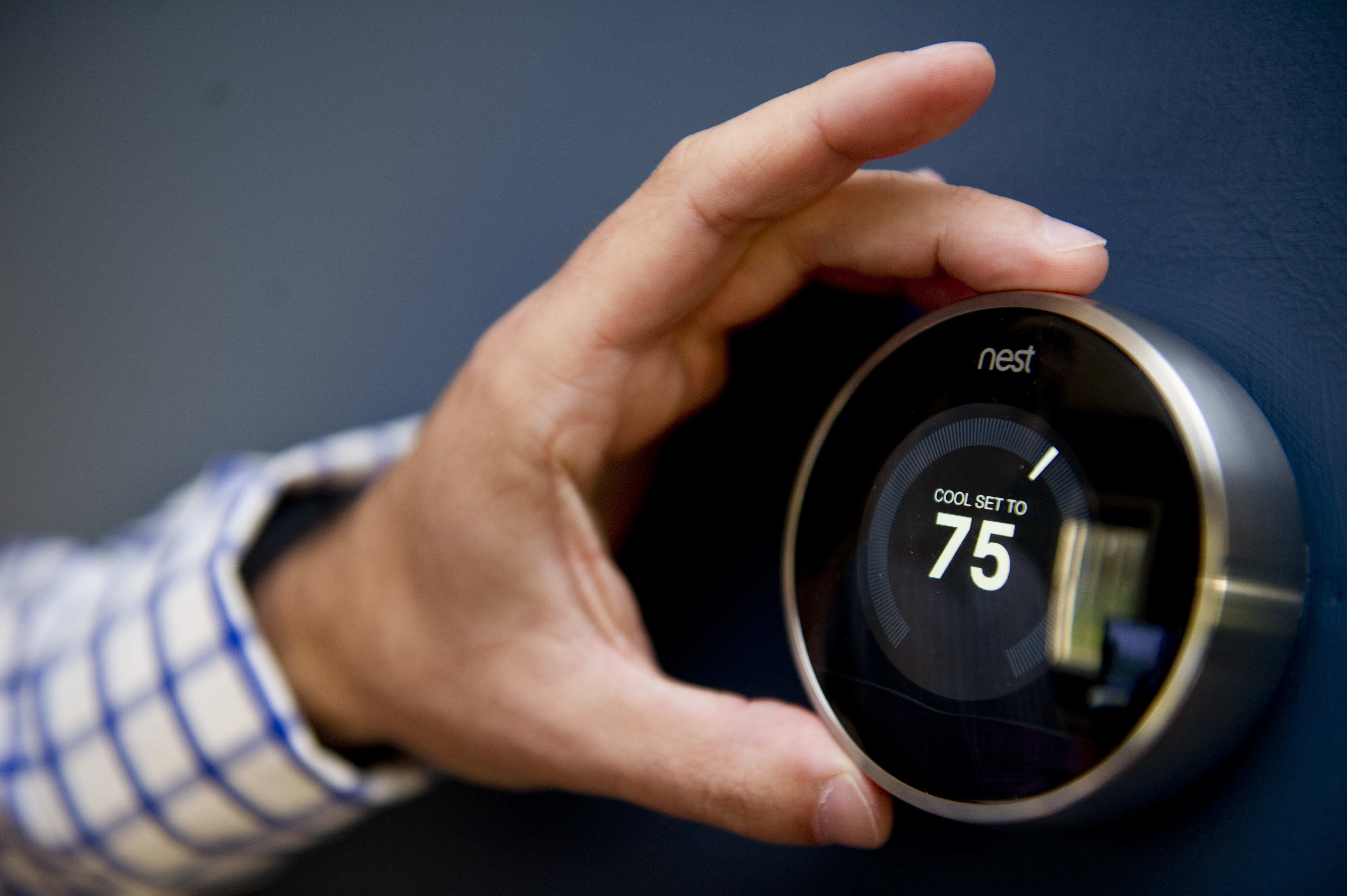 Nick DeLena adjusts his thermostat from Nest Labs in his home on August 12, 2013 in West Newbury, Massachusetts.