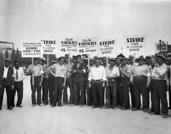 circa 1930:  Full-length image of a group of strikers from the Construction Workers Union holding signs while picketing for higher wages.  (Photo by Lambert/Getty Images)