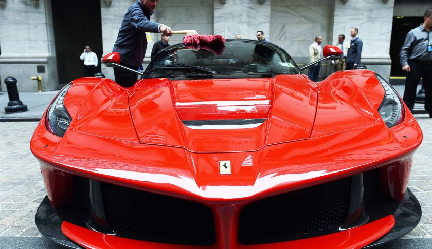 An employee shines a Ferrari in front of the New York Stock Exchange.