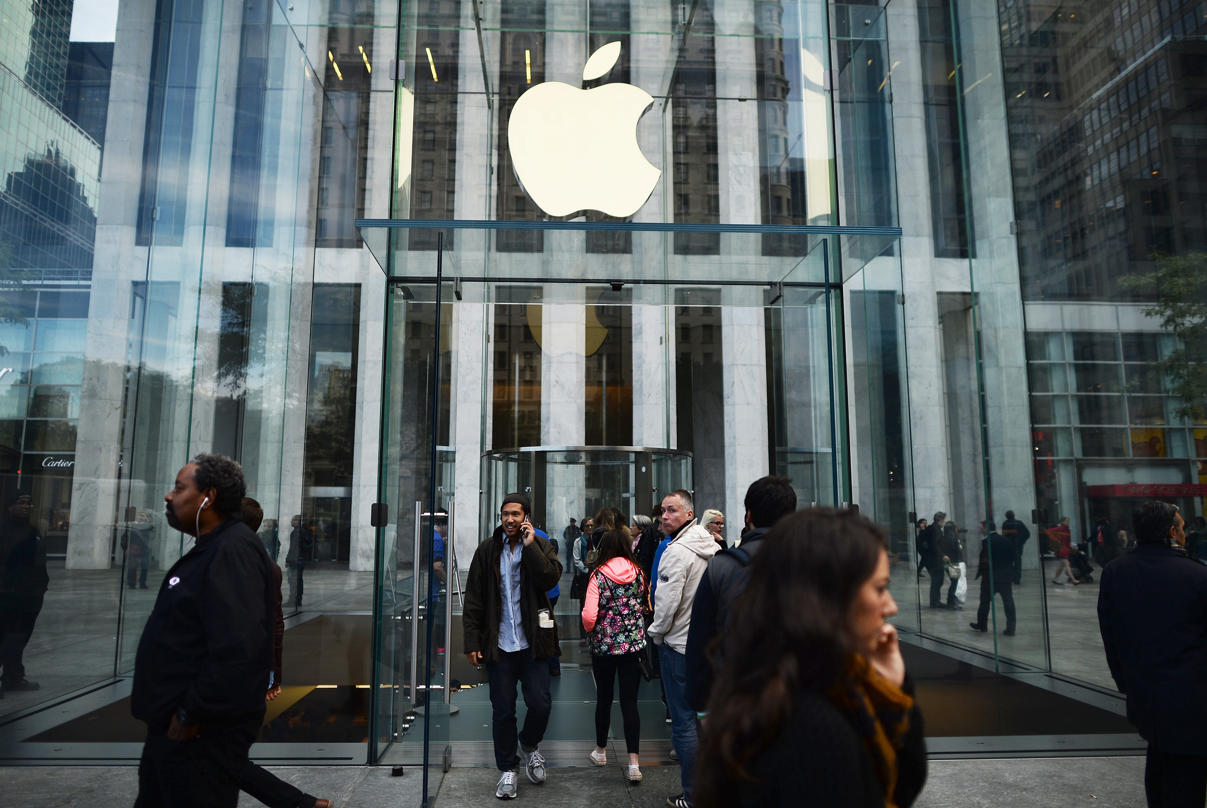 People walk past an Apple store in New York on October 20, 2014.