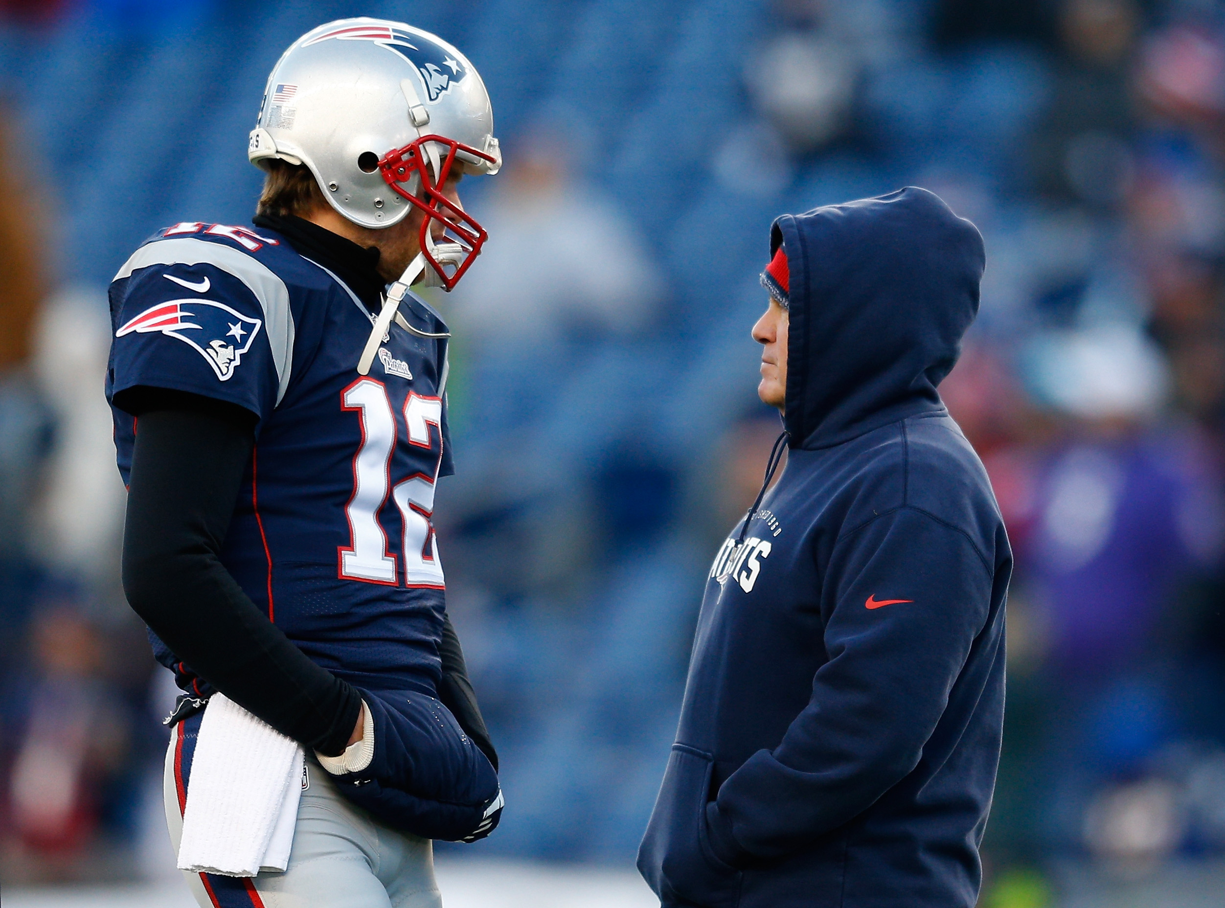 Tom Brady #12 and head coach Bill Belichick of the New England Patriots talk before the 2014 AFC Divisional Playoffs game against the Baltimore Ravens at Gillette Stadium on January 10, 2015 in Foxboro, Massachusetts