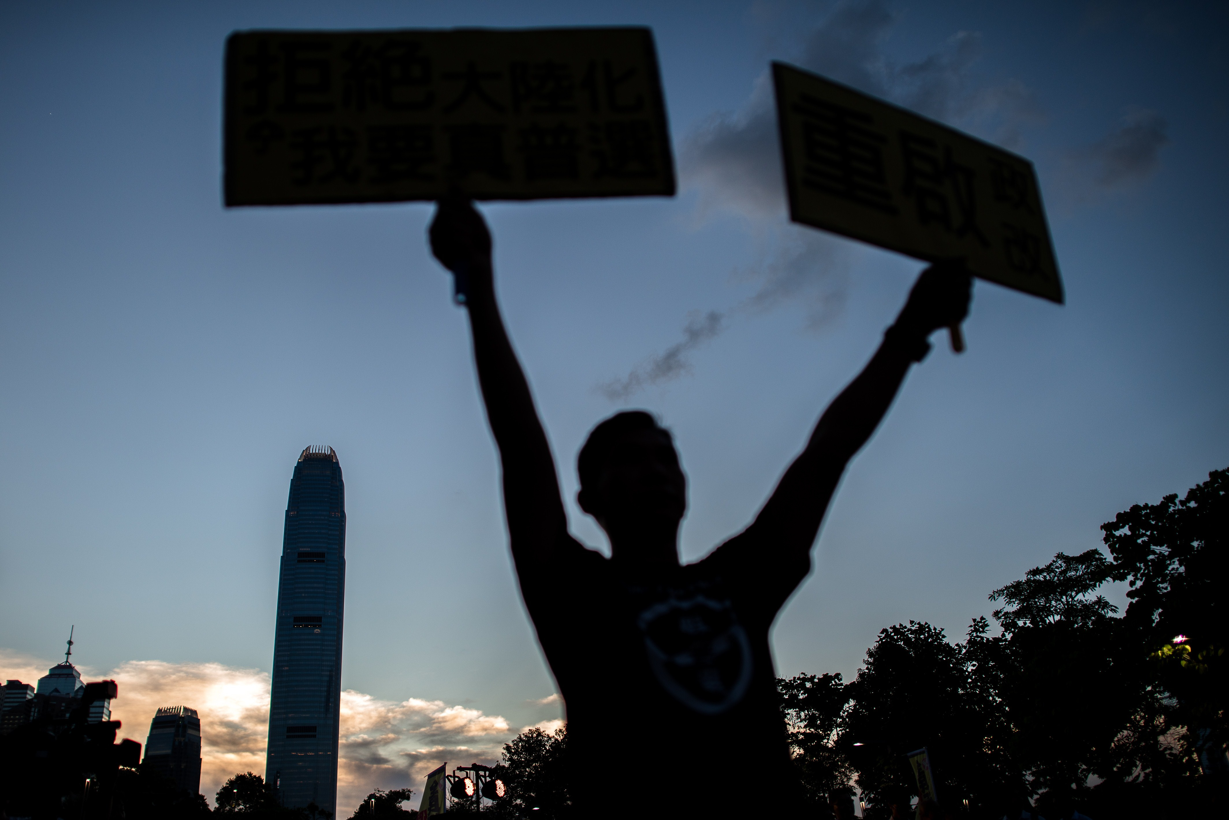A pro-democracy campaigner holds placard during sunset outside the city's legislature in Hong Kong on June 15, 2015, ahead of a key vote on the government's controversial political reform package.