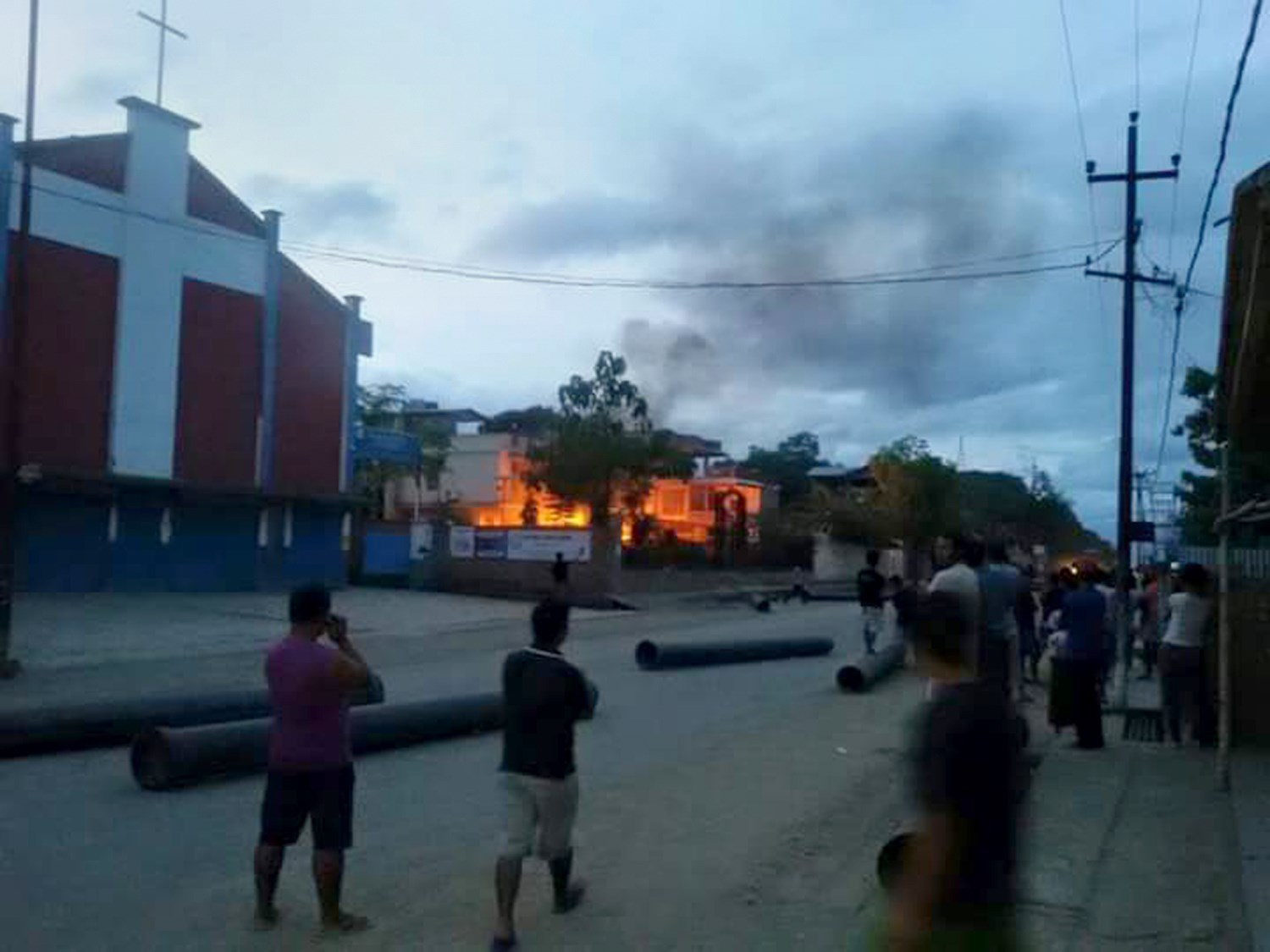 People watch a blaze at the residence of Manipur State Health Minister Phungzaphang Tonsimg, which was torched during a protest against controversial tribal-rights laws at Churachandpur, India, on Aug. 31, 2015