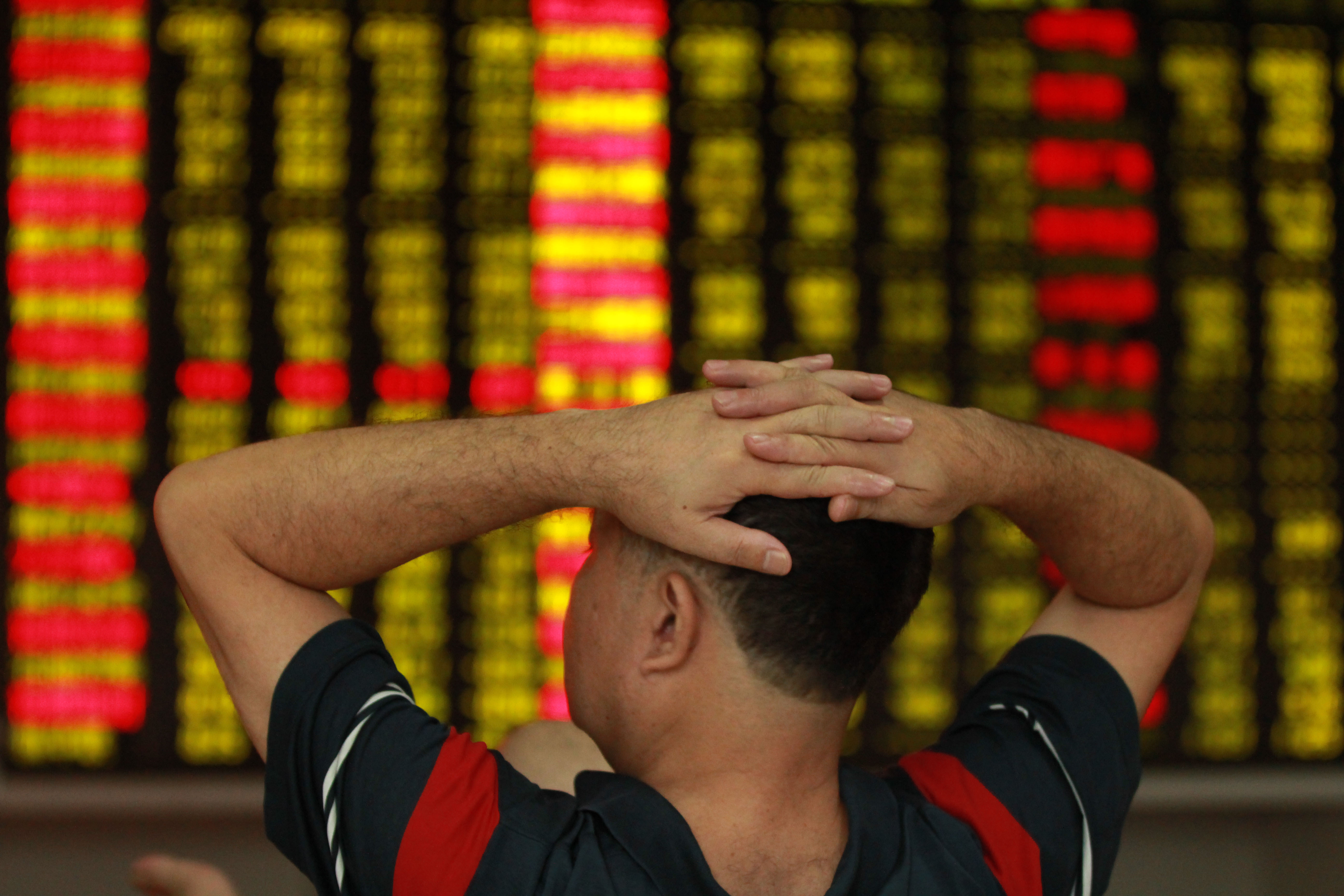 An investor observes stock market at a stock exchange hall on September 2, 2015 in Haikou, Hainan Province of China.