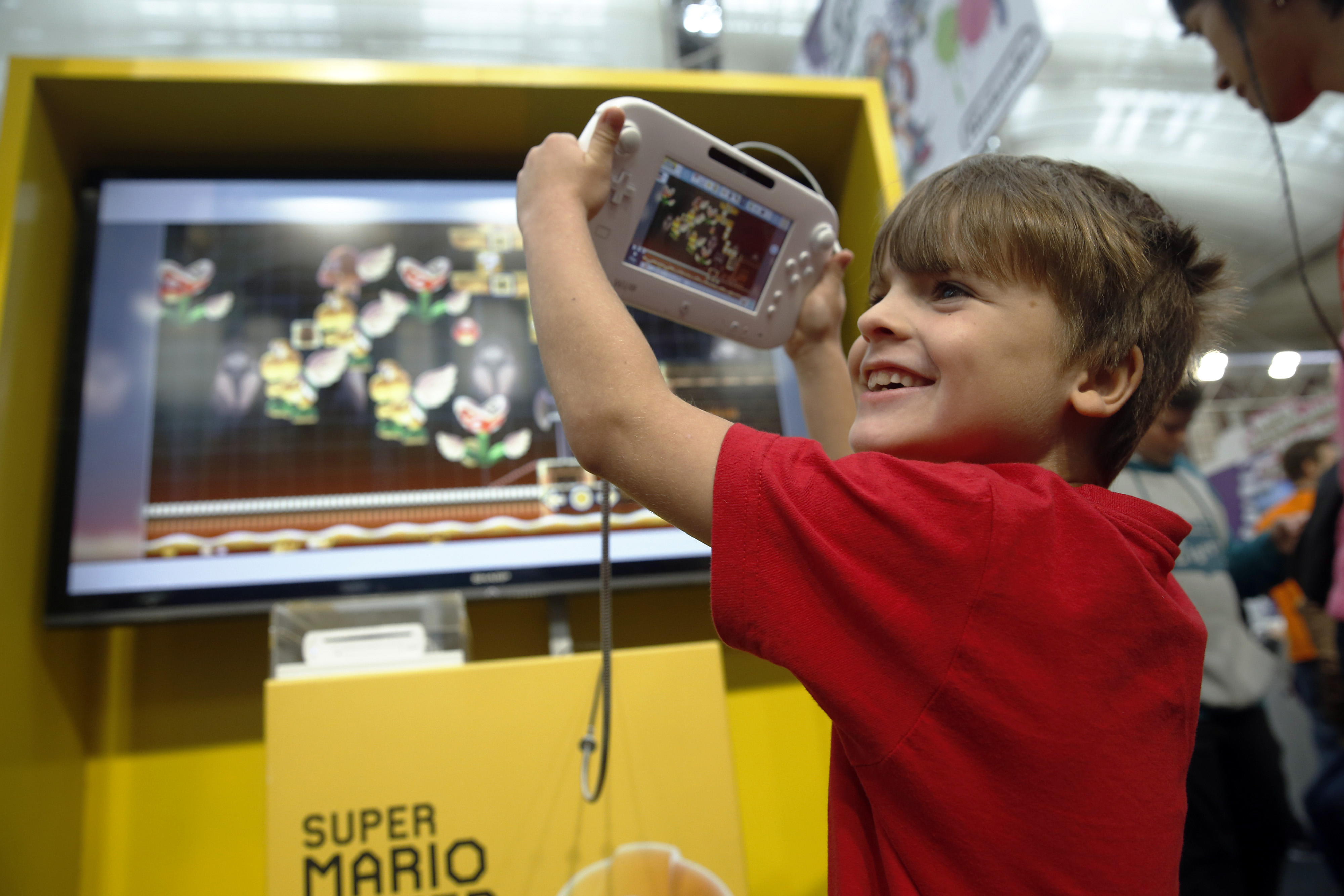 A visitor reacts as he plays Super Mario Maker, developed and published by Nintendo Co. for the Wii U, at the Legends of Gaming Live event in London, on Saturday, Sept. 5, 2015.