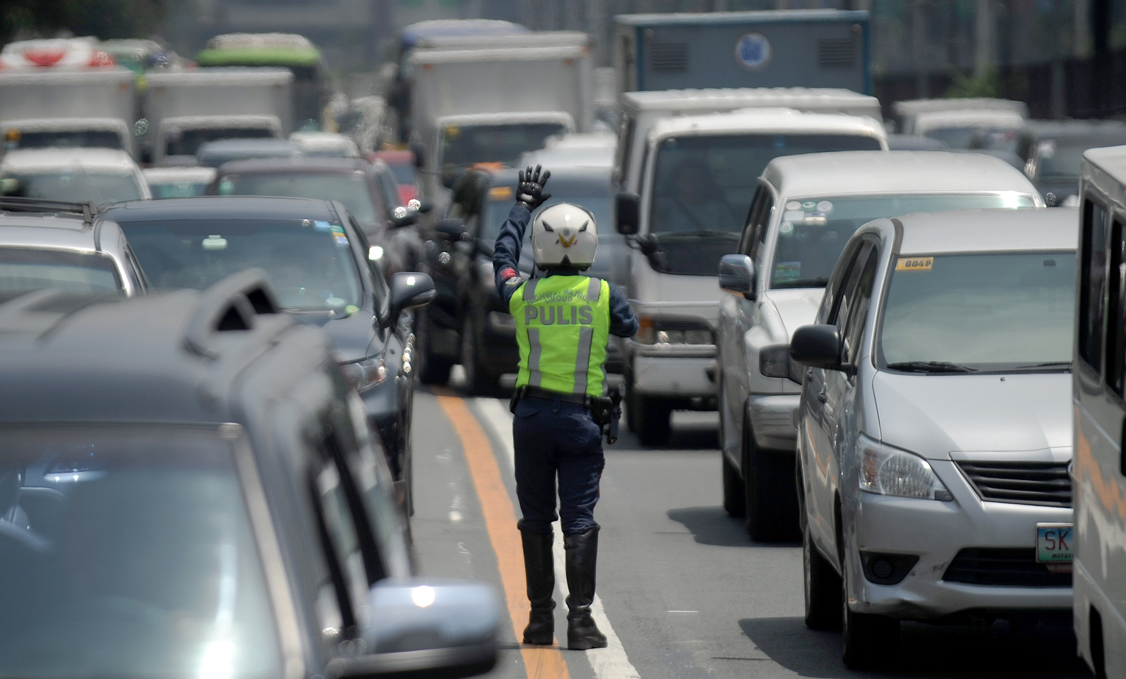 A police officer controls traffic at Epifanio de los Santos Avenue, popularly known as EDSA, in Manila on Sept. 8, 2015