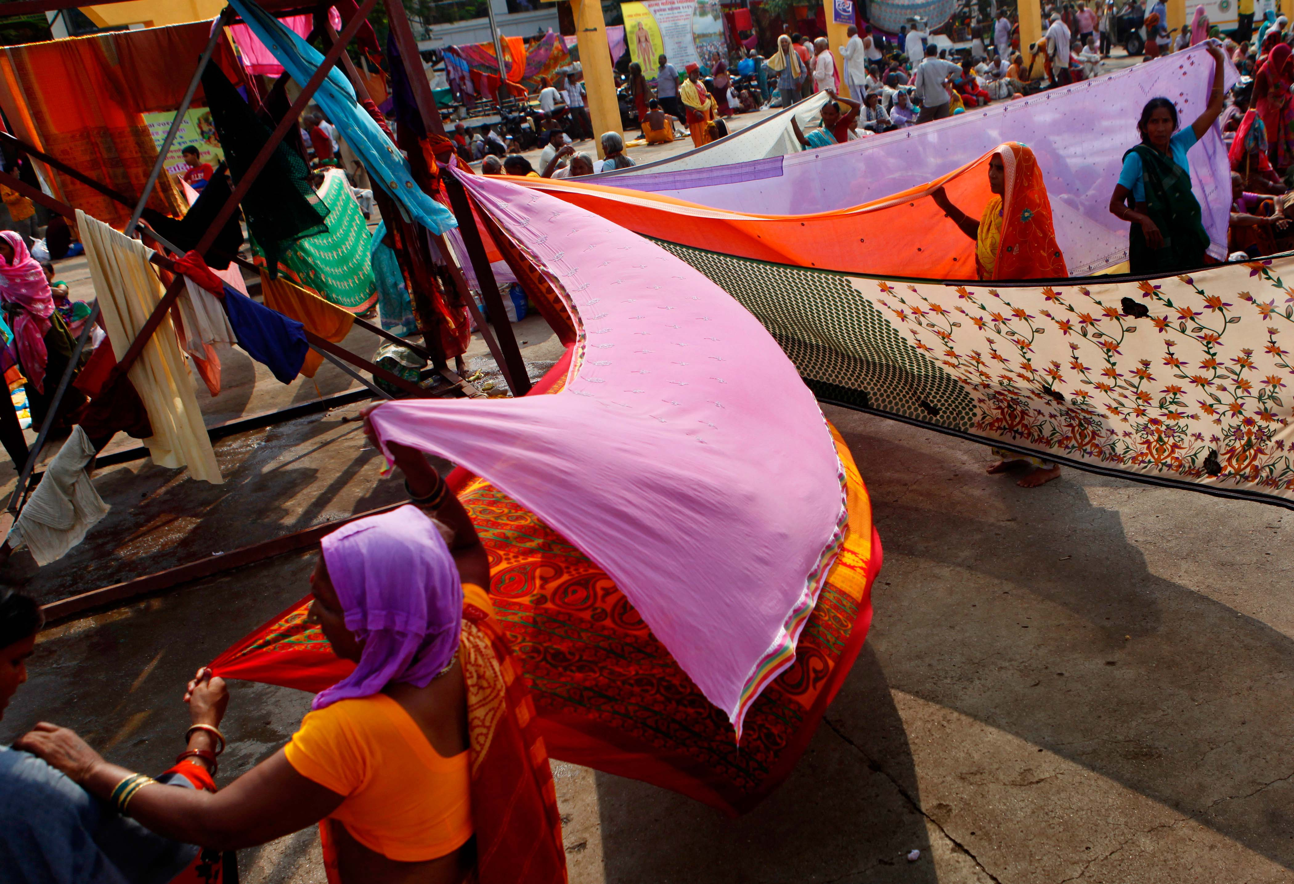 Devotees drying their clothes after the holy dip in the river Godavari on the eve of second Shahi Snan of Simhastha Kumbh Mela at Ramghat in Nashik, India, on Sept. 12, 2015.