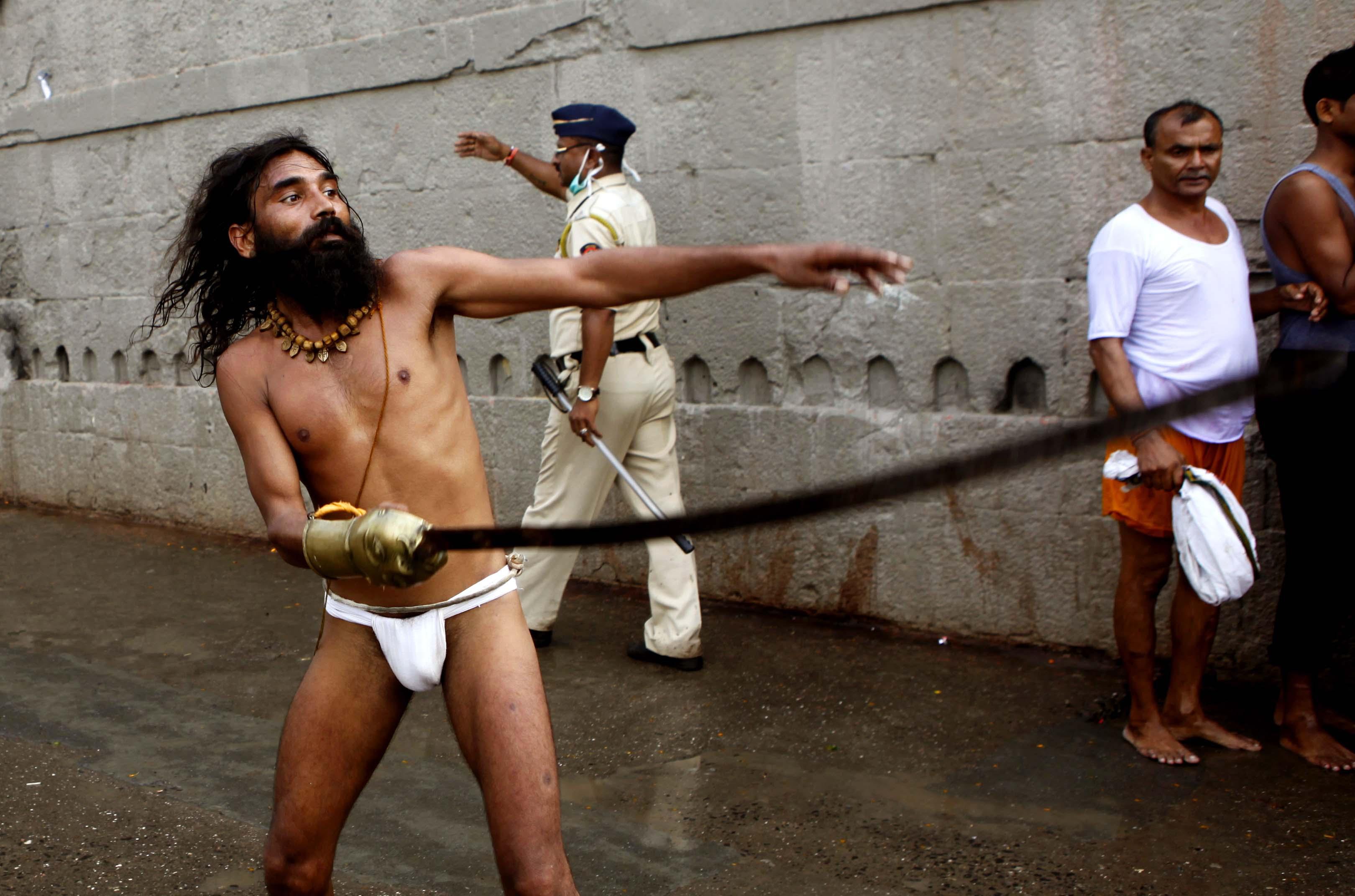 A sadhu showing sword tricks during the second Shahi Snan of Simhastha Kumbh Mela in Nashik, India, on Sept. 13, 2015.