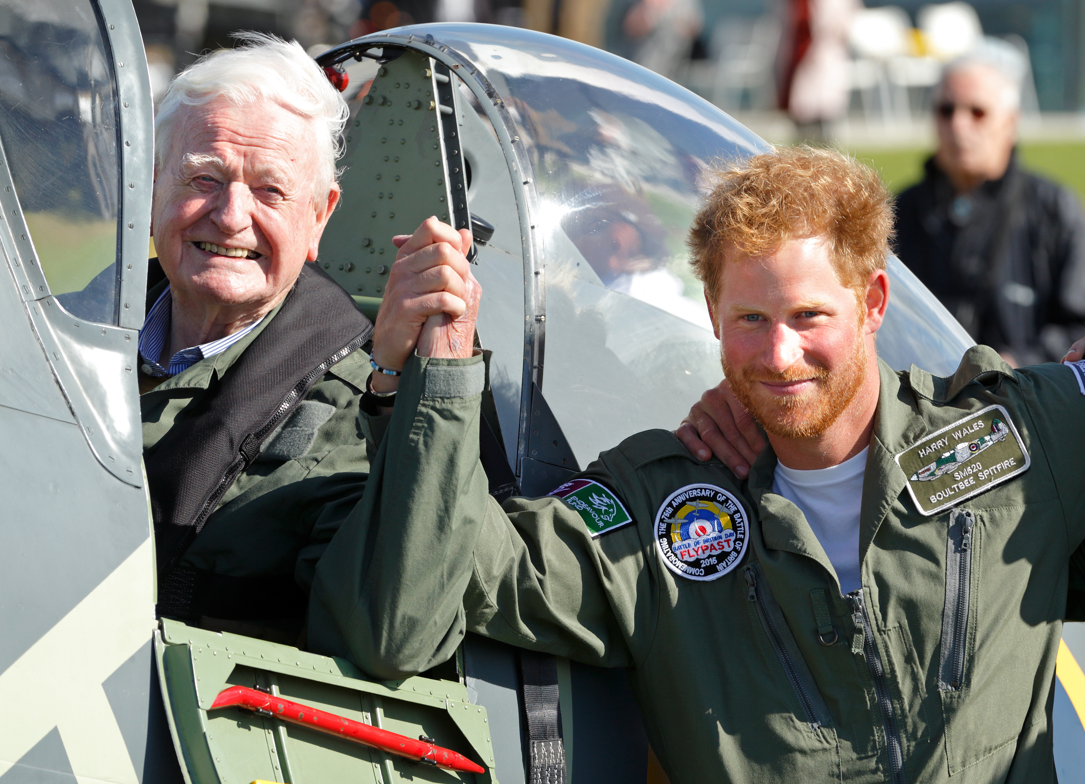 Prince Harry holds hands with 95-year-old Battle of Britain veteran Tom Neil after he landed back at Goodwood Aerodrome in his Spitfire aircraft following a Battle of Britain Flypast on Sept. 15, 2015, in Chichester, England