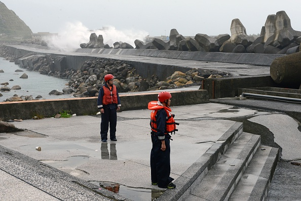 Taiwanese coast guards keep watch on the coastline of Keelung on September 28, 2015, as typhoon Dujuan approaches