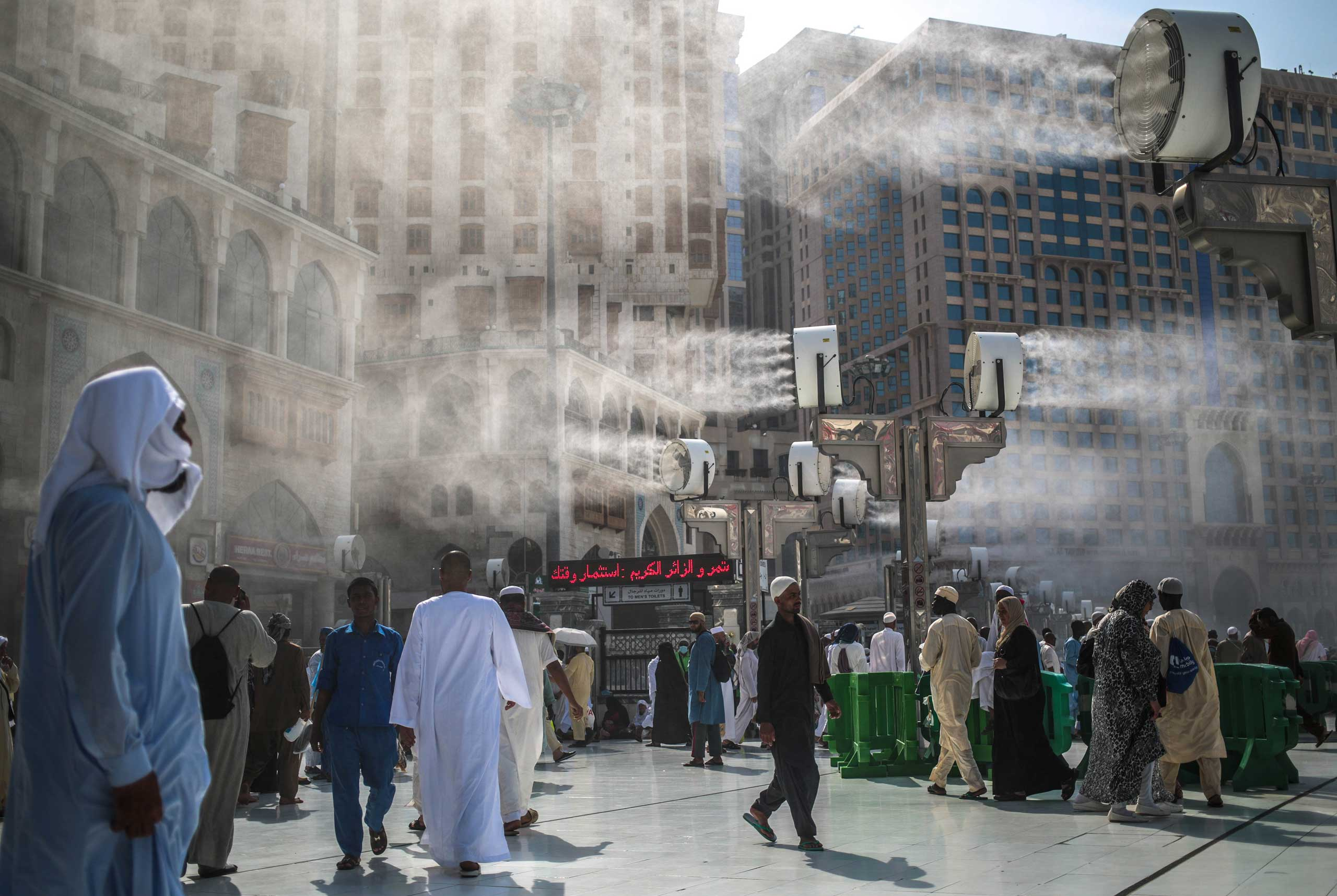 Water is sprayed over Muslim pilgrims to cool them down during the afternoon heat as they walk outside the Grand Mosque in the holy city of Mecca, on Sept. 15, 2015.