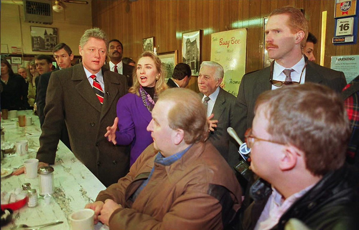 Democratic presidential candidate Bill Clinton (L) and his wife Hillary (C) refute allegations at the Busy Bee Cafe in Chicago that she has profited from Arkansas' state fund, in a picture taken Mar. 16, 1992.