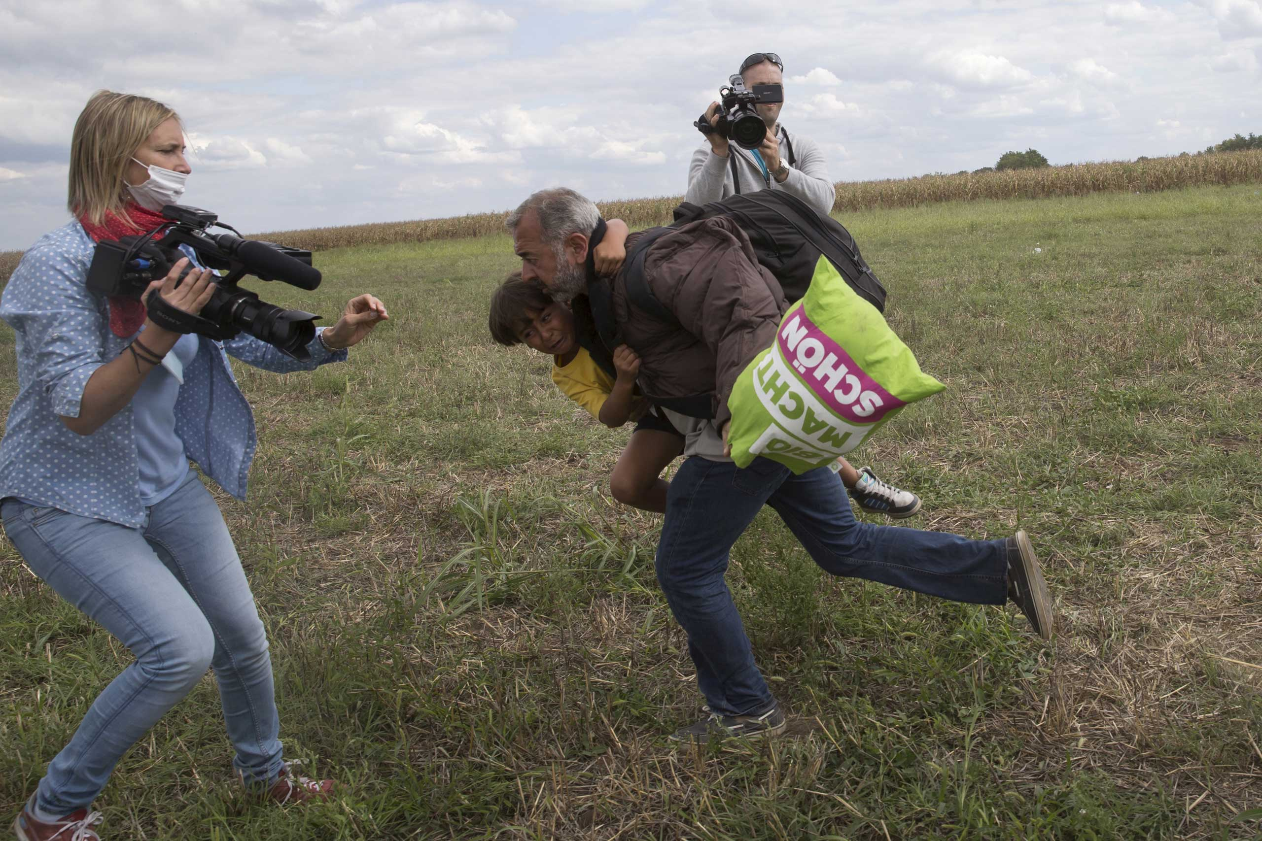 A migrant runs with a child before tripping on TV camerawoman Petra Laszlo (L) and falling as he tries to escape from a collection point in Roszke village, Hungary, Sept. 8, 2015