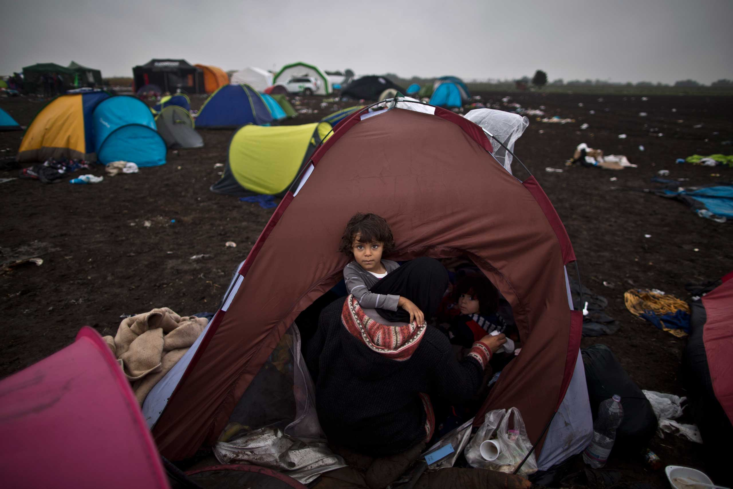 Syrian refugee child Zaid Hussein, 4, is held by his mother while sitting inside their tent at a makeshift camp for asylum seekers in Roszke, on Sept. 11, 2015.