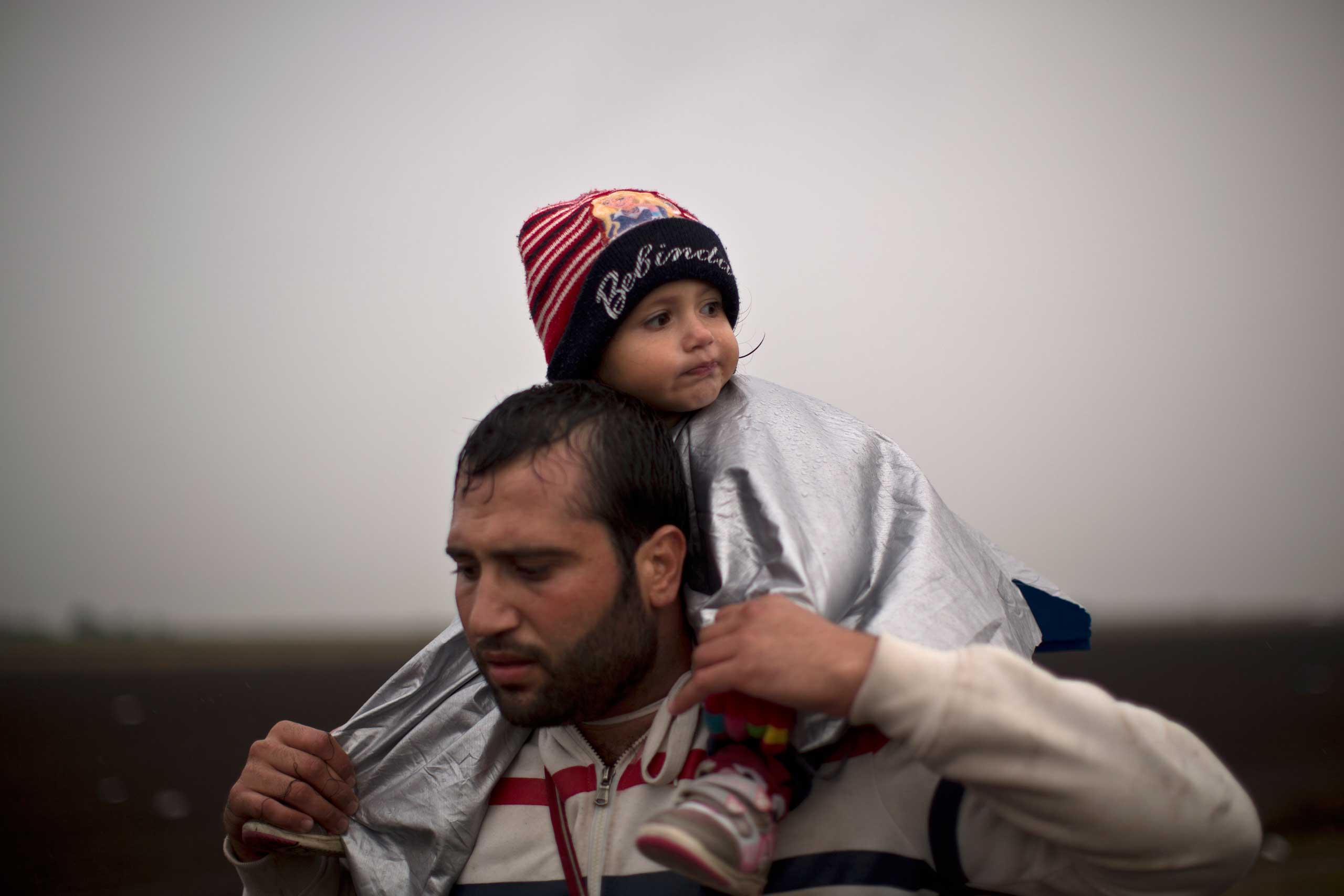 A man carrying his daughter on his shoulder walks on a railway toward a makeshift camp for asylum seekers in Roszke, on Sept. 10, 2015.