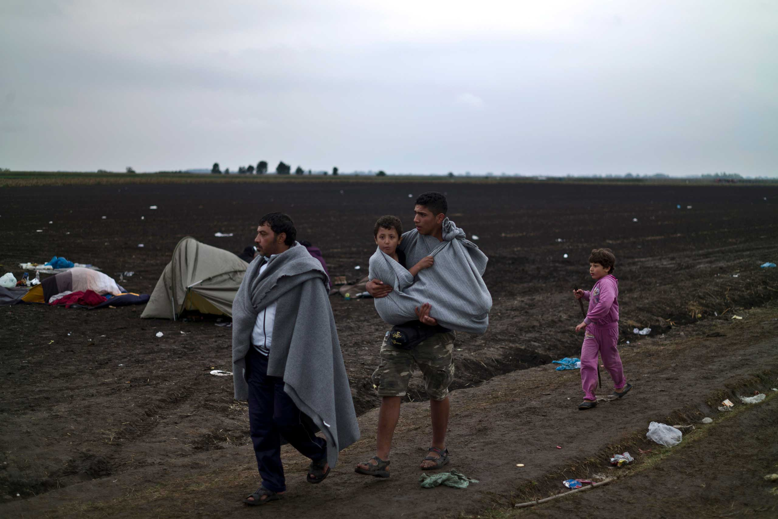 Syrian refugee Hussein Sbaih, 18, center, carries his cousin Saifuallah, 7, whose legs are broken, after they crossed the Serbian-Hungarian border near Roszke, on Sept. 11, 2015.