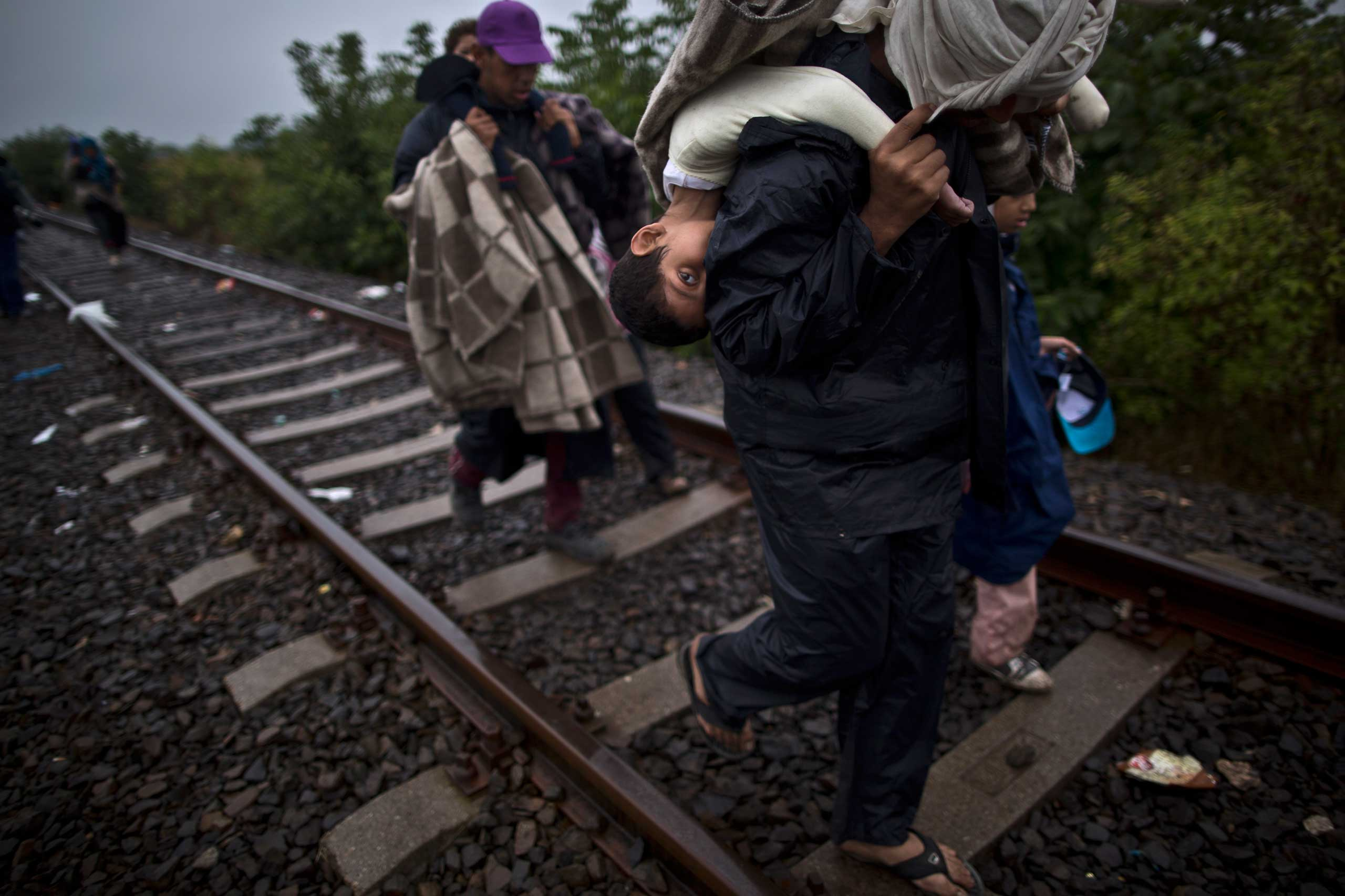 Bara'ah Alhammadi, 10, a Syrian refugee, is carried on the back of her father as they make their way along a railway track after they crossed the Serbian-Hungarian border near Roszke, on Sept. 11, 2015.