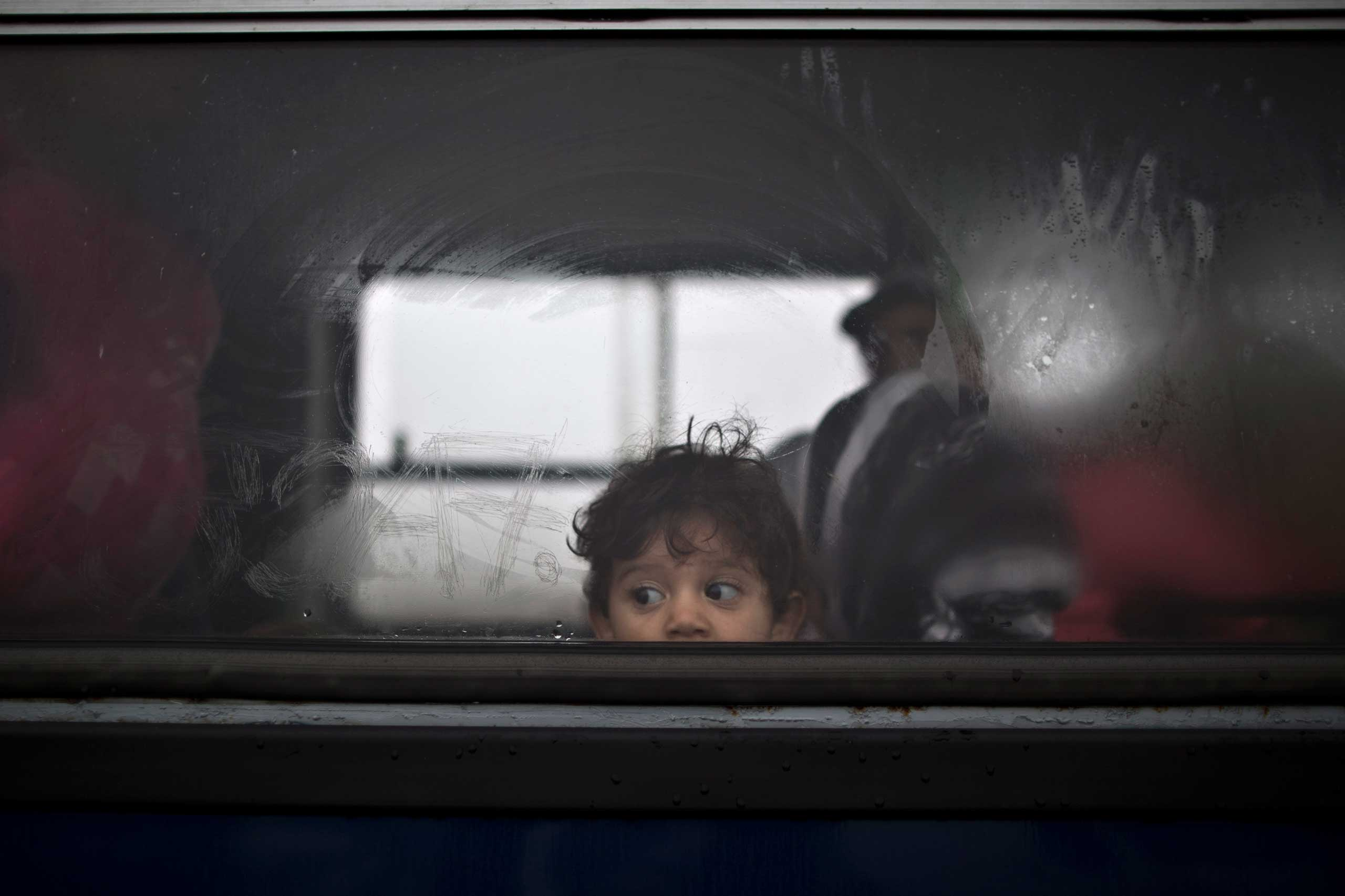 A Syrian refugee child looks out of a bus that will take him and his family to the center for asylum seekers near Roszke, on Sept. 11, 2015.