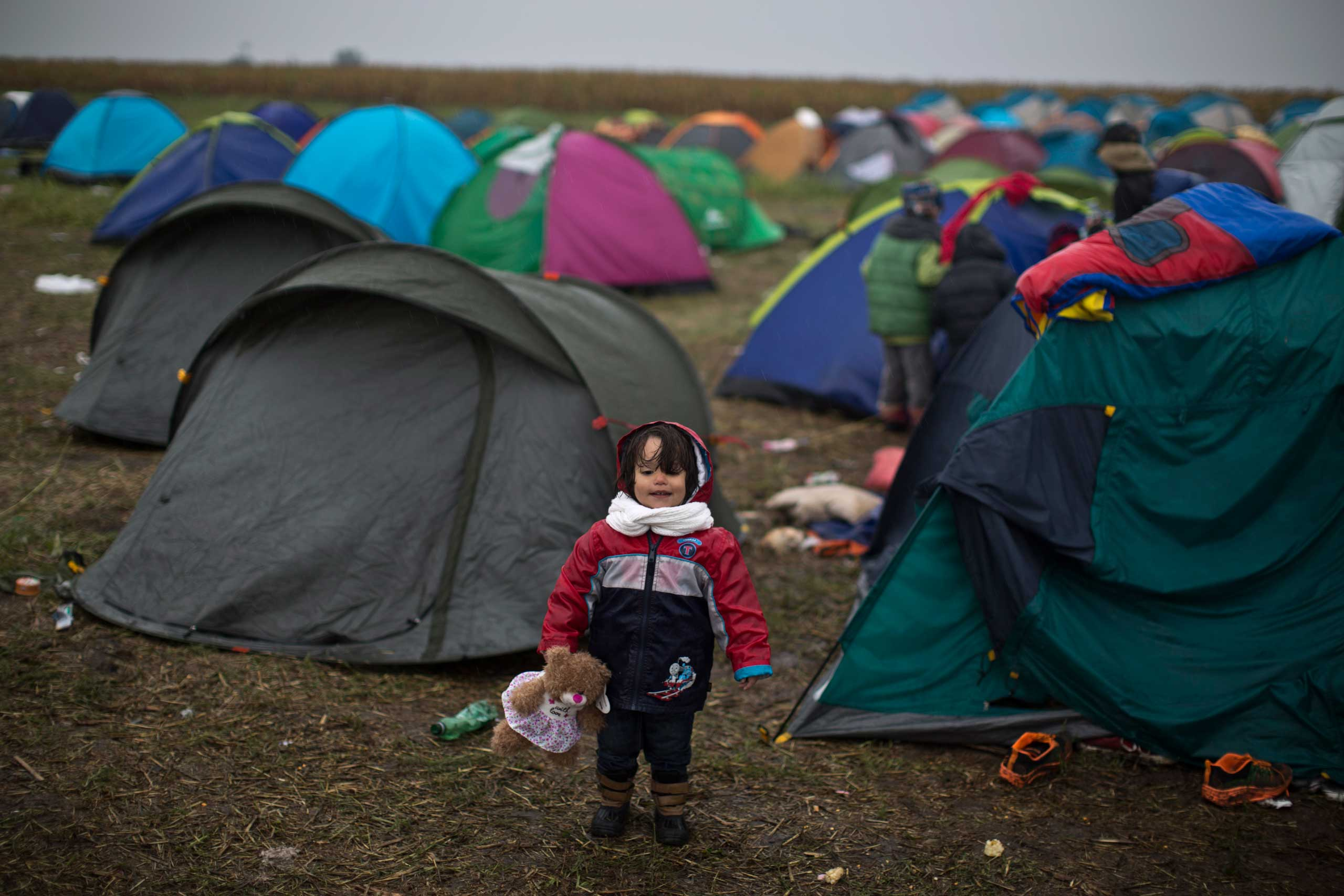 Syrian refugee child Jana Makkiyeh, 3, whose family comes from Damascus, Syria, holds a teddy bear while standing near her family's tent at a makeshift camp for asylum seekers in Roszke, on Sept. 10, 2015.