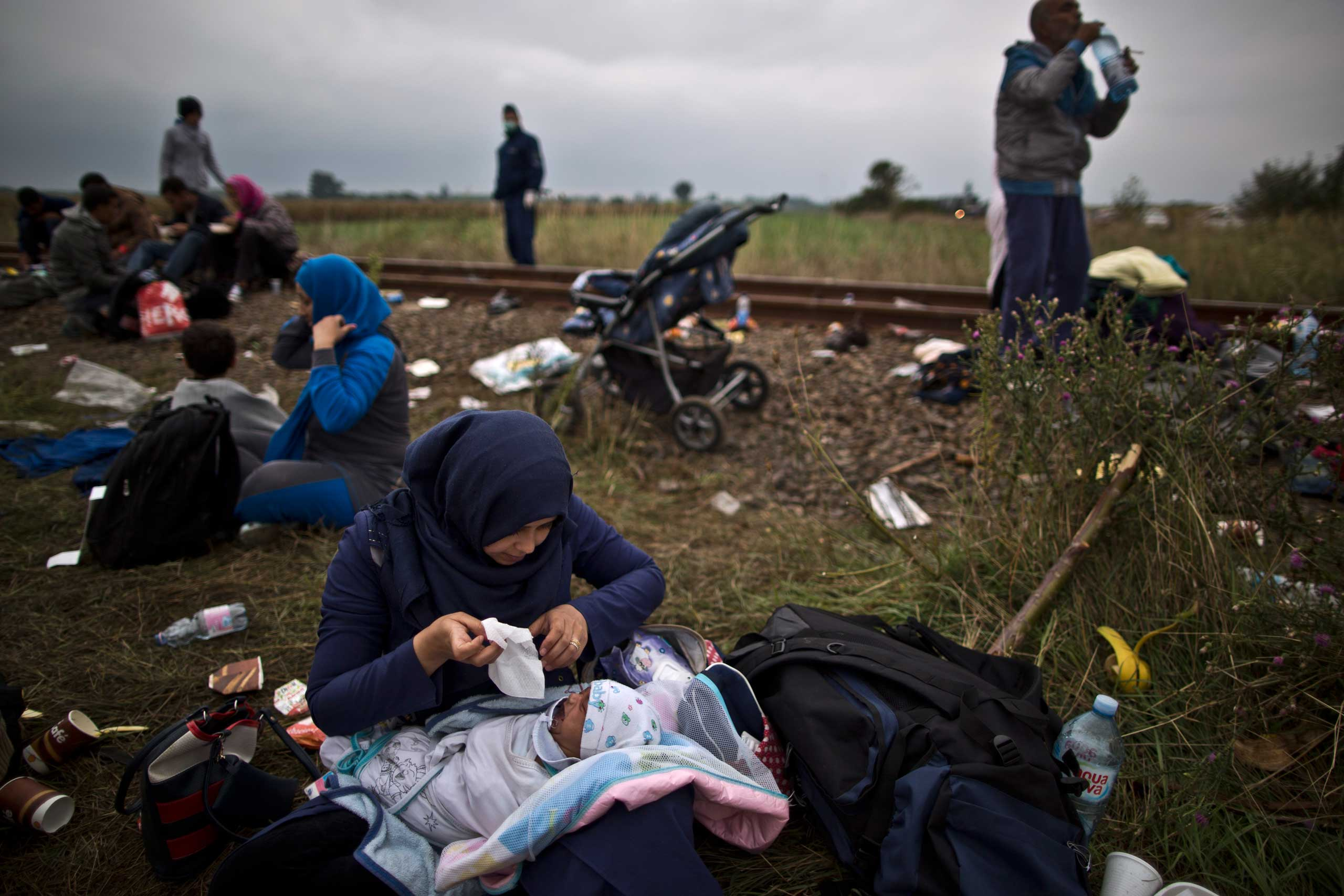 Iraqi refugee Umm Fadil tends to her crying son Ahmad, 41 days, while resting by a railway track after they crossed the Serbian-Hungarian border near Roszke, on Sept. 11, 2015.