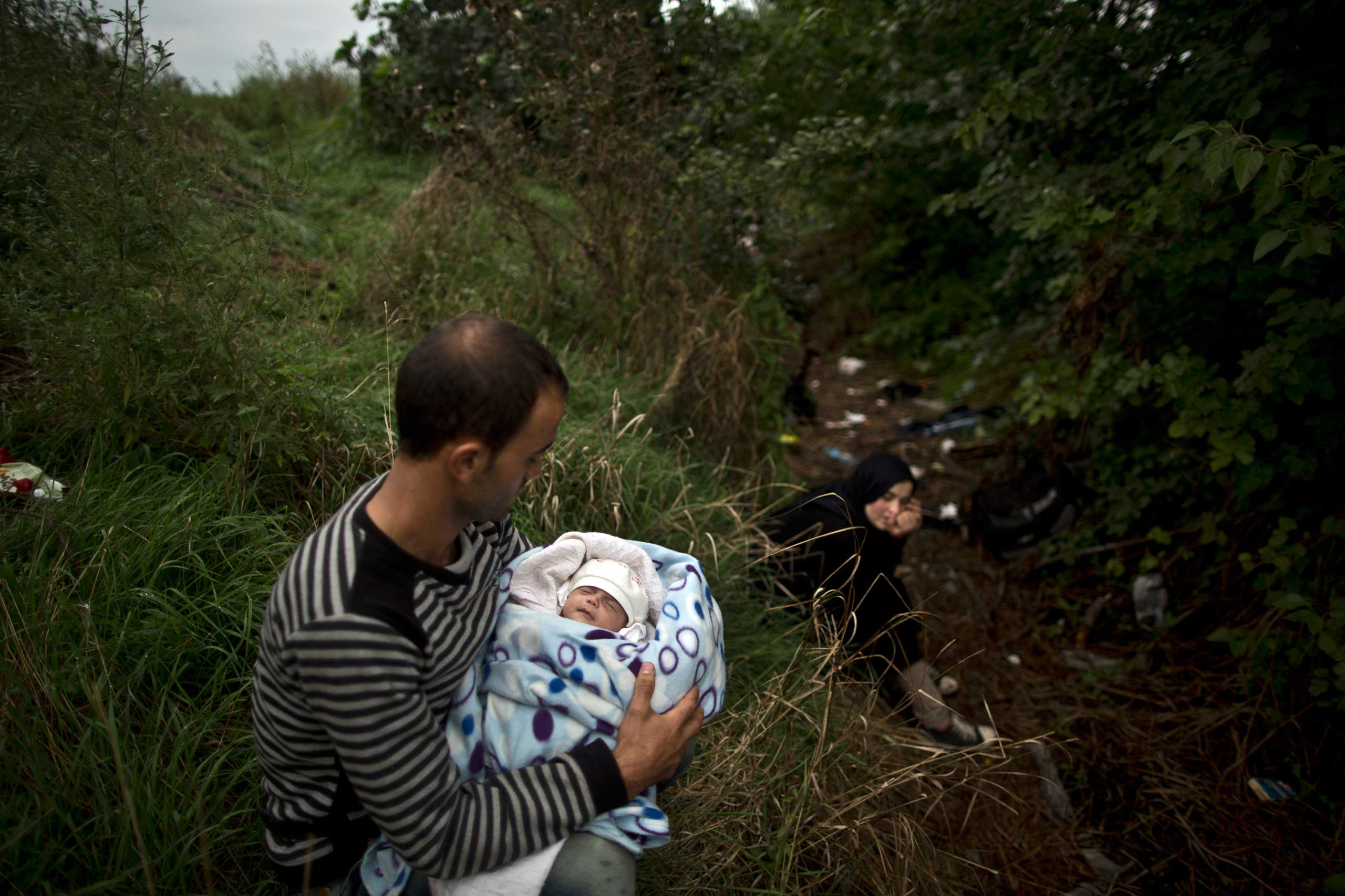 Syrian refugee Raed Alabdou, 24, holds his one-month old daughter Roa'a, while he and his wife hide in a field not to be seen by Hungarian policemen, after they crossed the Serbian-Hungarian border near Roszke, southern Hungary, on Sept. 11, 2015.