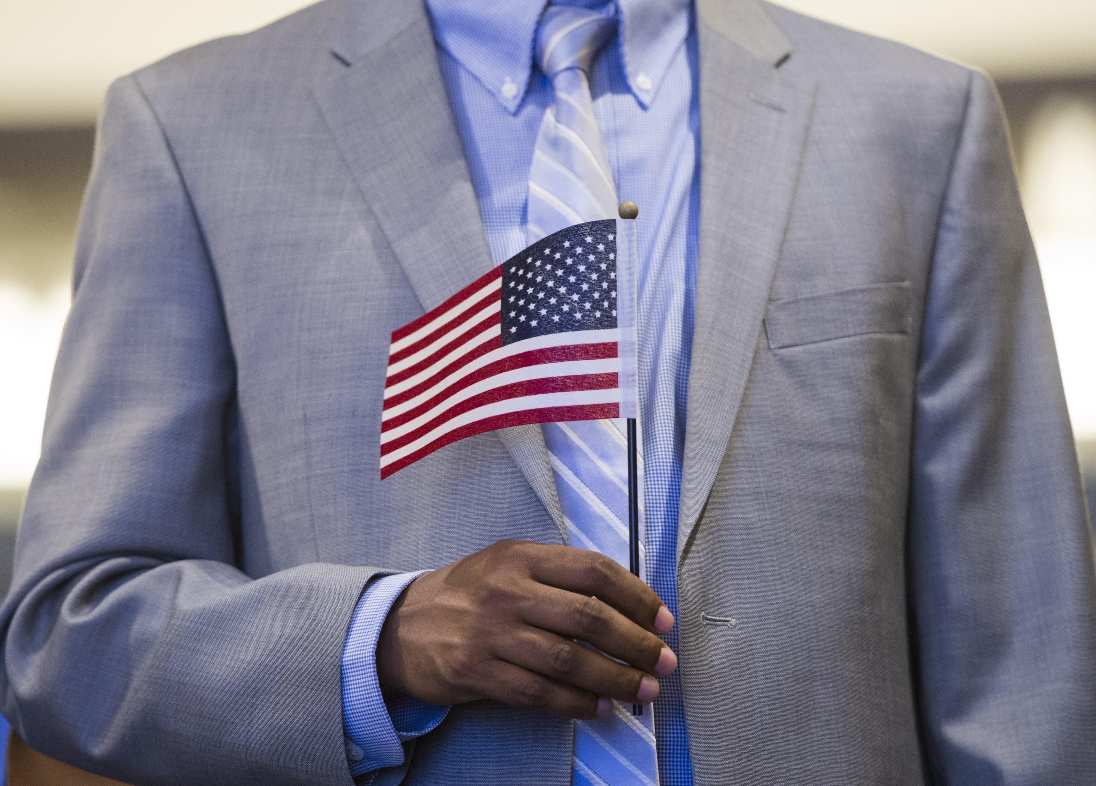 A man holds an American flag prior to taking the citizenship oath to become a U.S. citizen during a naturalization ceremony in Alexandria, Virginia in May.