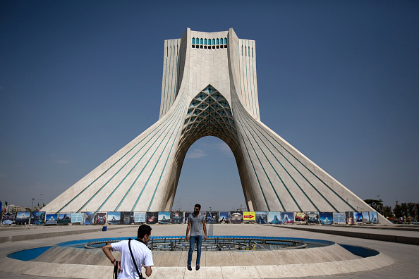 An Iranian tourist poses for a photograph in front of the Azadi tower in Tehran, Iran, on Friday, Aug. 21, 2015.