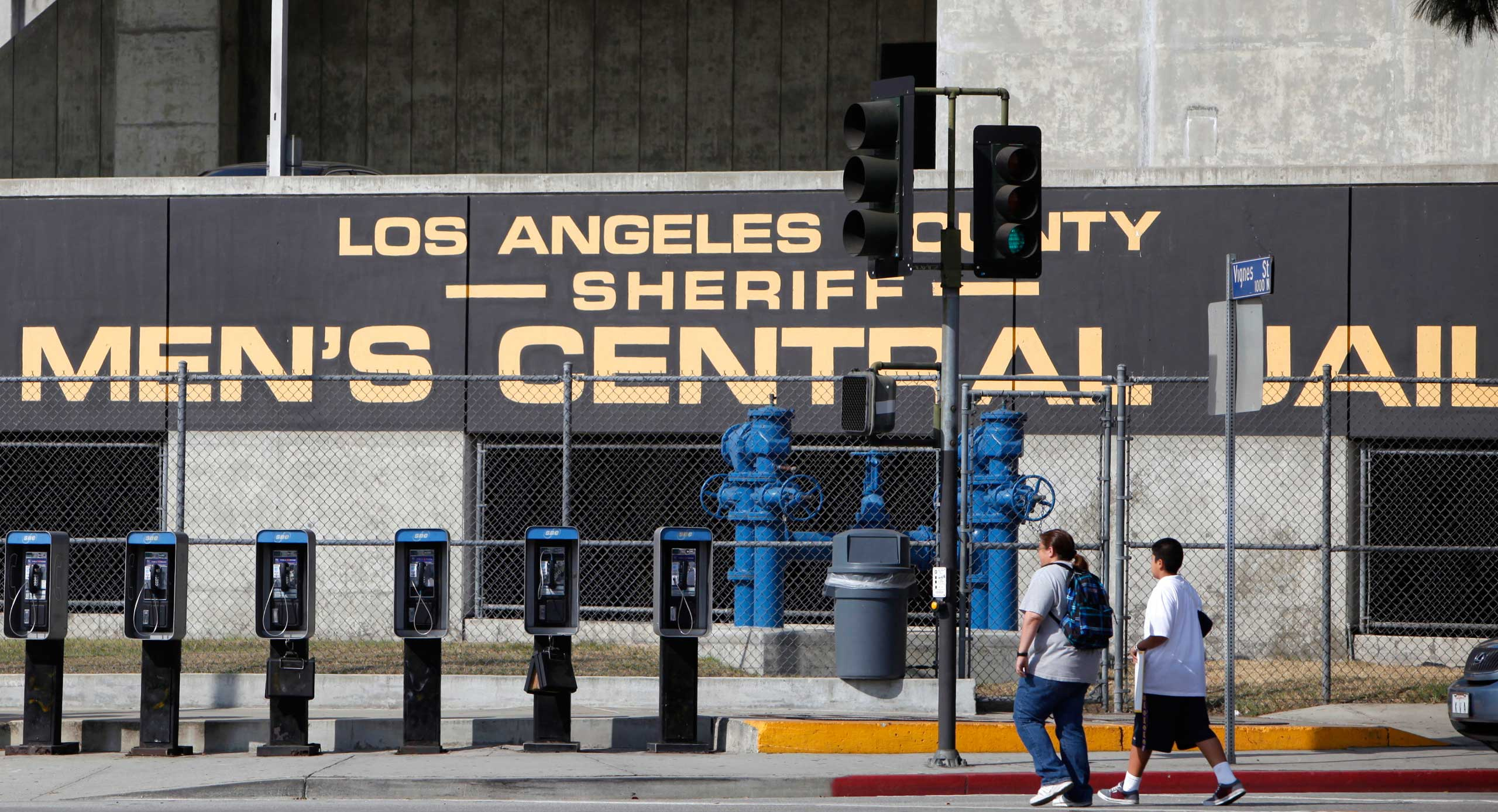 People walk past the Los Angeles County Sheriff's Men's Central Jail facility in Los Angeles.