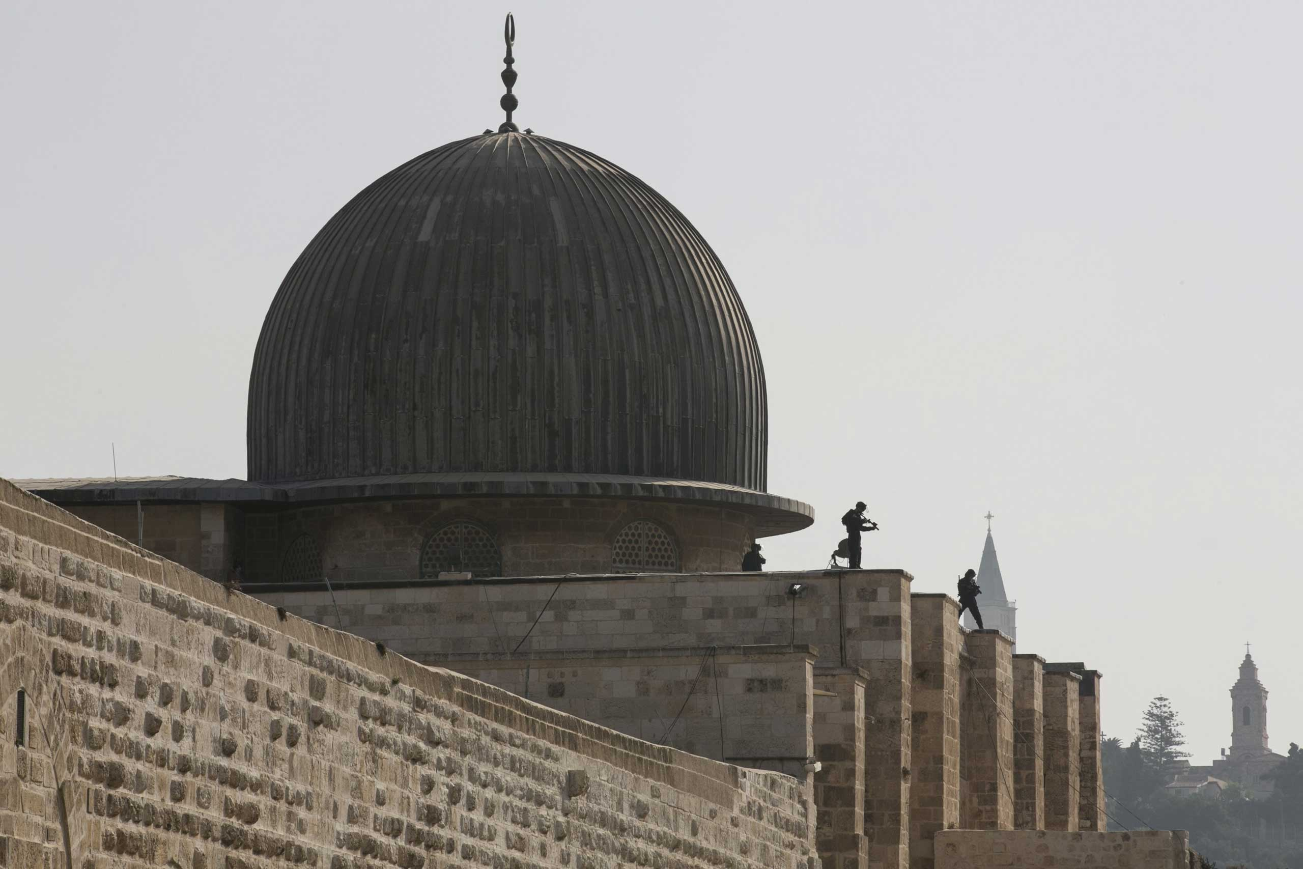 Israeli police officers take positions on the roof of the Al-Aqsa mosque during clashes with Palestinians in Jerusalem's Old City, on Sept. 15, 2015.