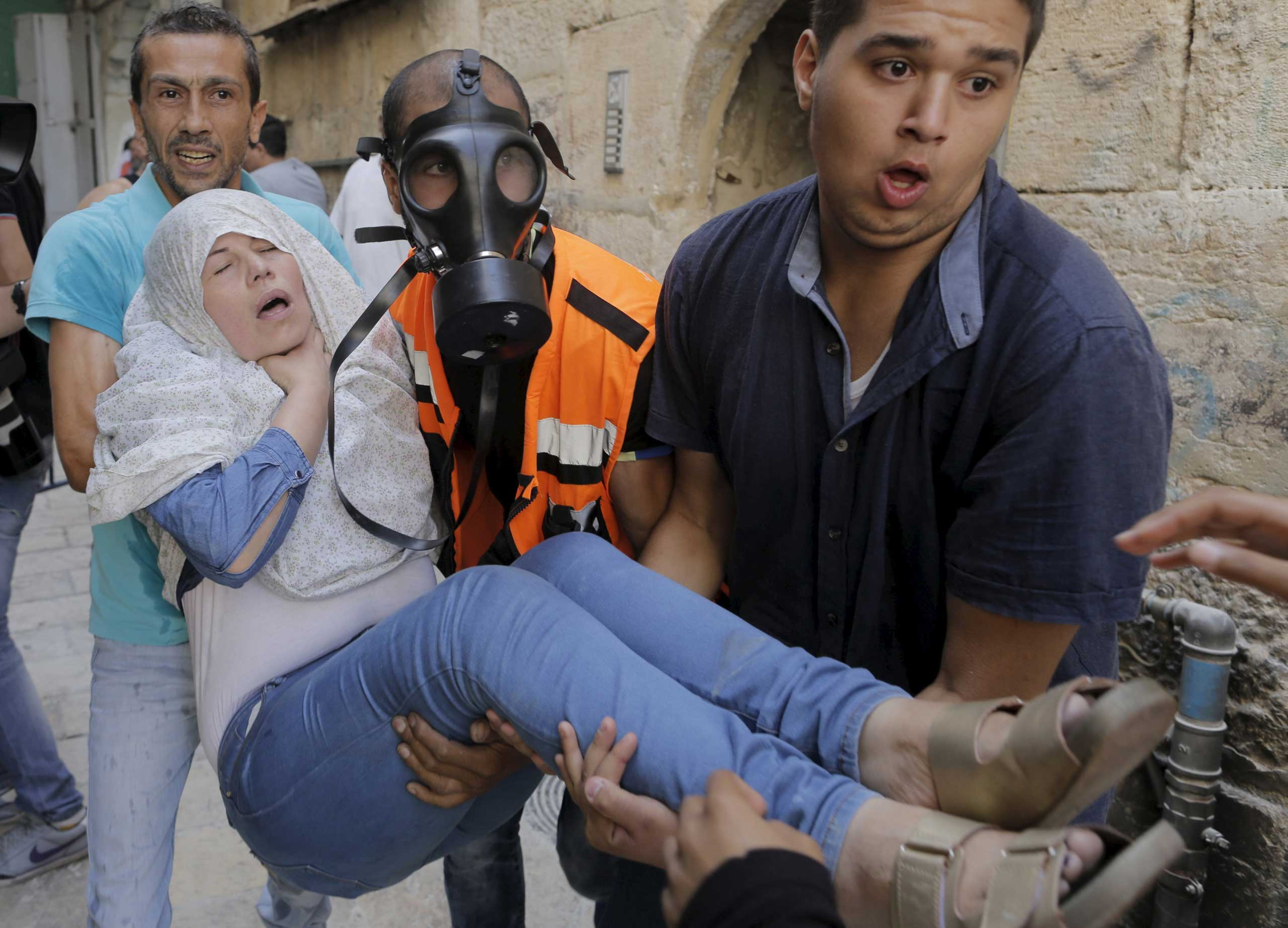 A Palestinian woman affected by tear gas is evacuated by medics during clashes between stone-throwing Palestinians and Israeli police in Jerusalem's Old City, on Sept. 15, 2015.