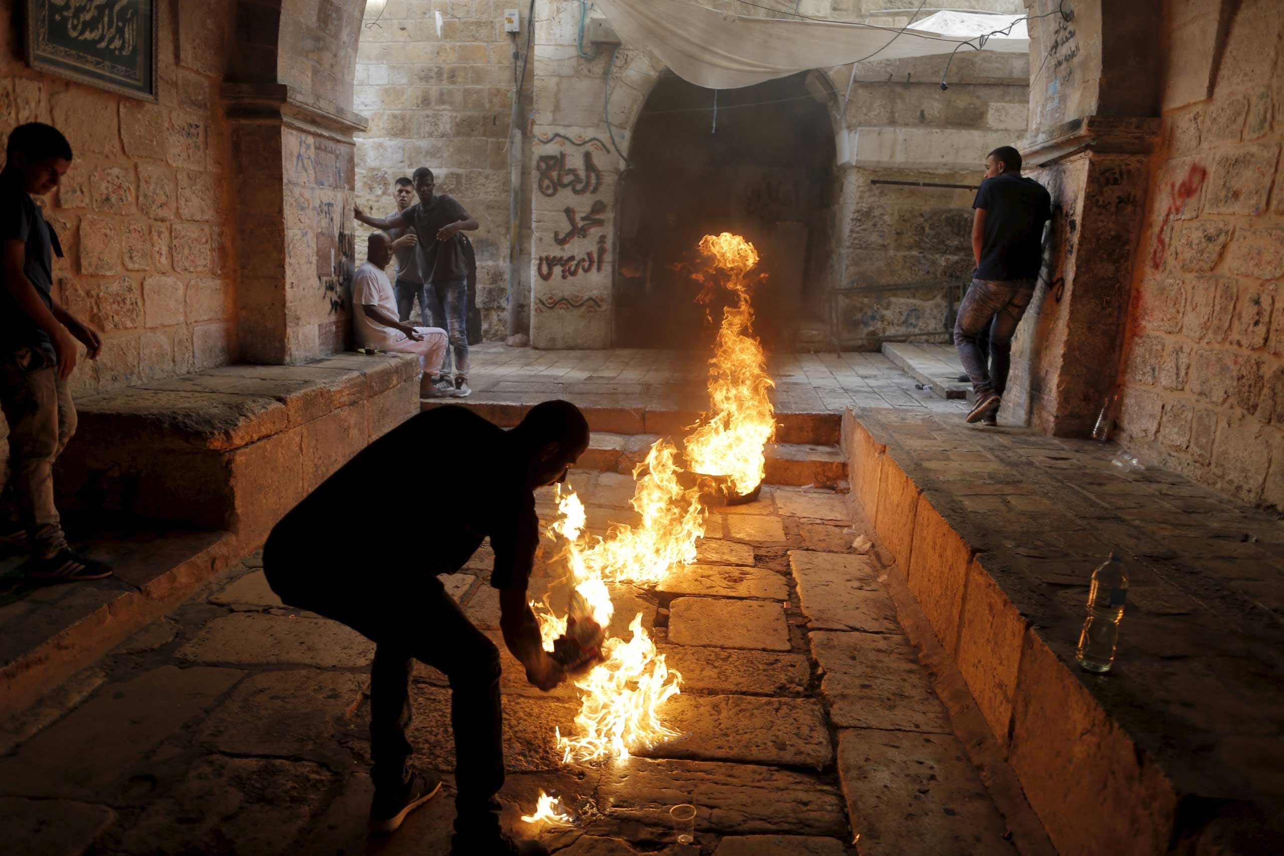 A Palestinian protester kicks a burning tyre during clashes between Palestinians and Israeli police officers in Jerusalem's Old City, on Sept. 15, 2015.