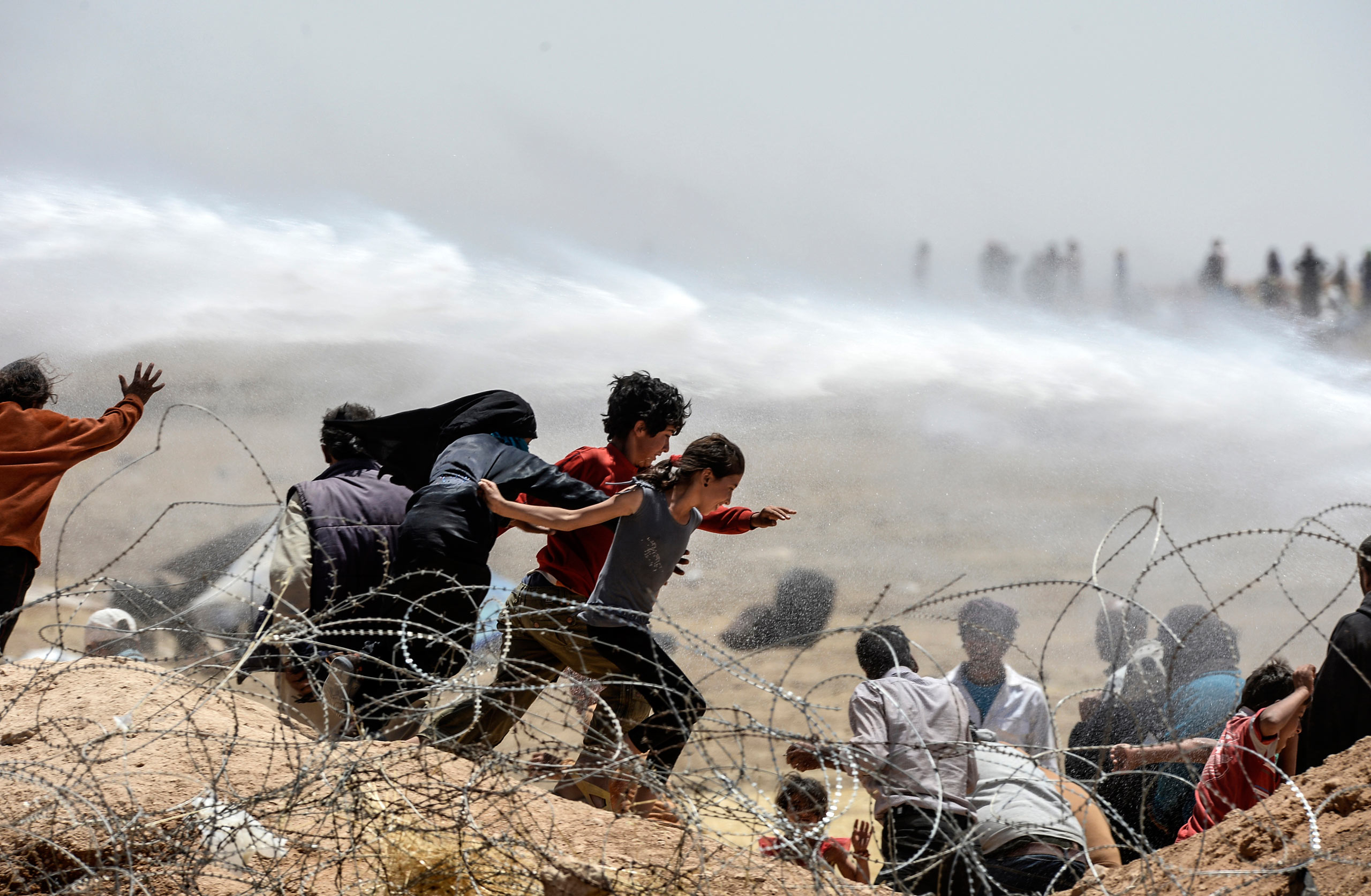 Syrian refugees run away as Turkish soldiers use water cannons to shove them from the wired fences at the Turkish border near the Syrian town of Tell Abyad and Akçakale, in the Şanlıurfa province. June 13, 2015.