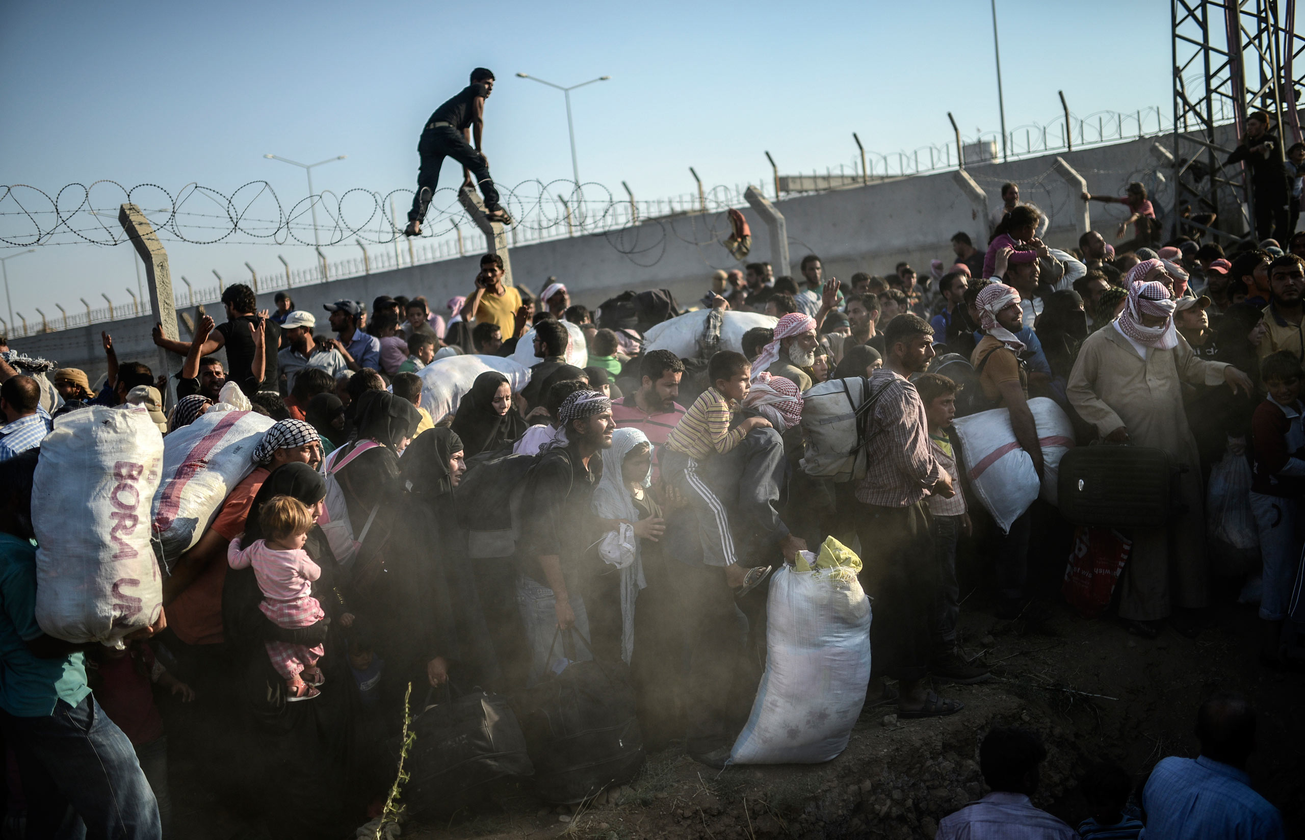 Syrians fleeing their war-torn country rush through the broken wire border fences entering illegally the Turkish territory, near the Turkish crossing gate in Akçakale, in the Şanlıurfa province. June 14, 2015.