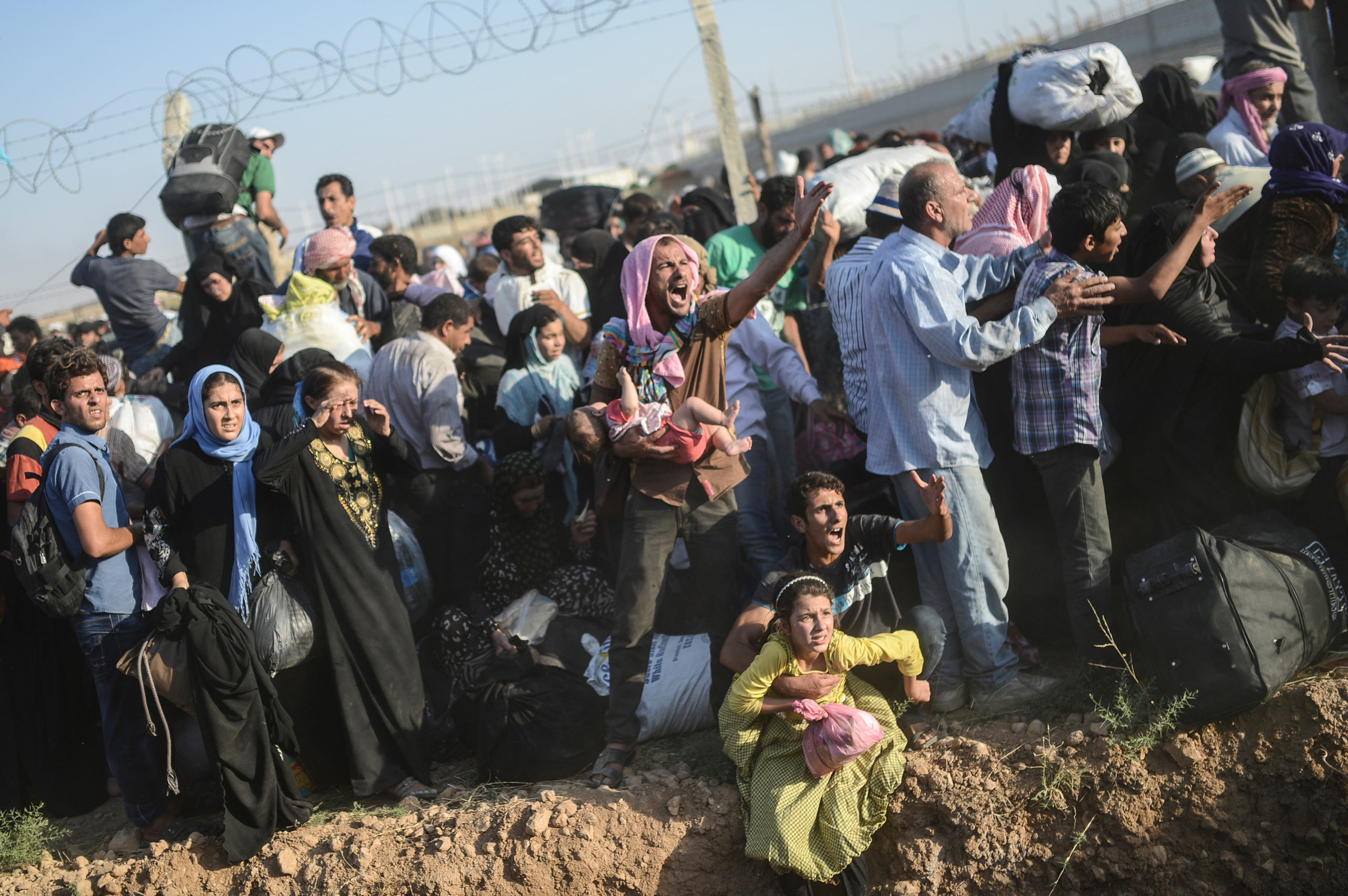Syrians fleeing their war-torn country rush through the broken border fences, entering illegally the Turkish territory, near the Turkish crossing gate in Akçakale, in the Şanlıurfa province. June 14, 2015.