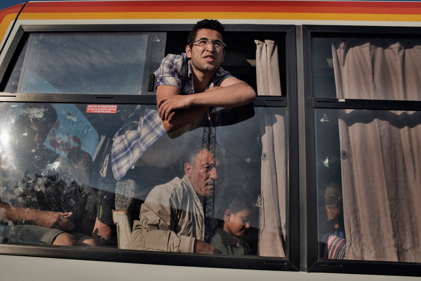 Ghafek Aiad Alsaho, a Syrian migrant, looks through the window of a police bus after border guards caught him crossing illegally from Serbia into Hungary on his way into the European Union.                               Roszke, Hungary, Aug. 29, 2015.