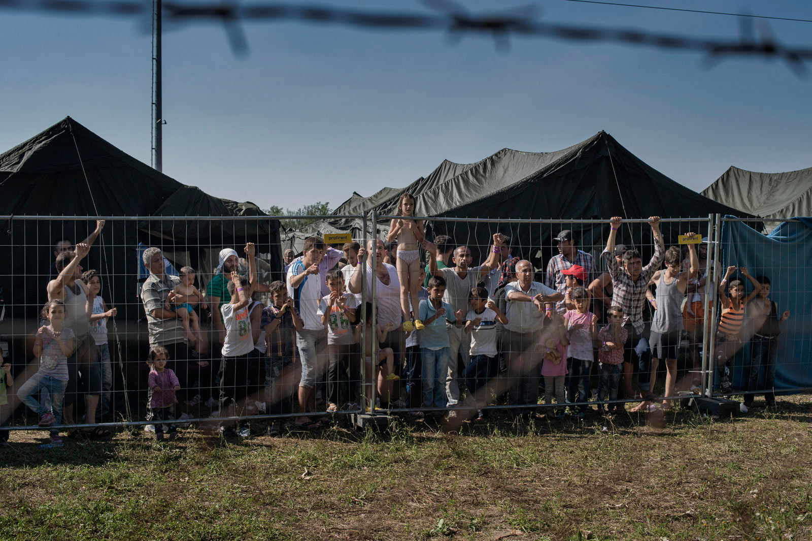 A group of migrants waits at a makeshift detention camp for Hungarian authorities to register their arrival in the European Union.                     Roszke, Hungary, Aug. 29, 2015.
